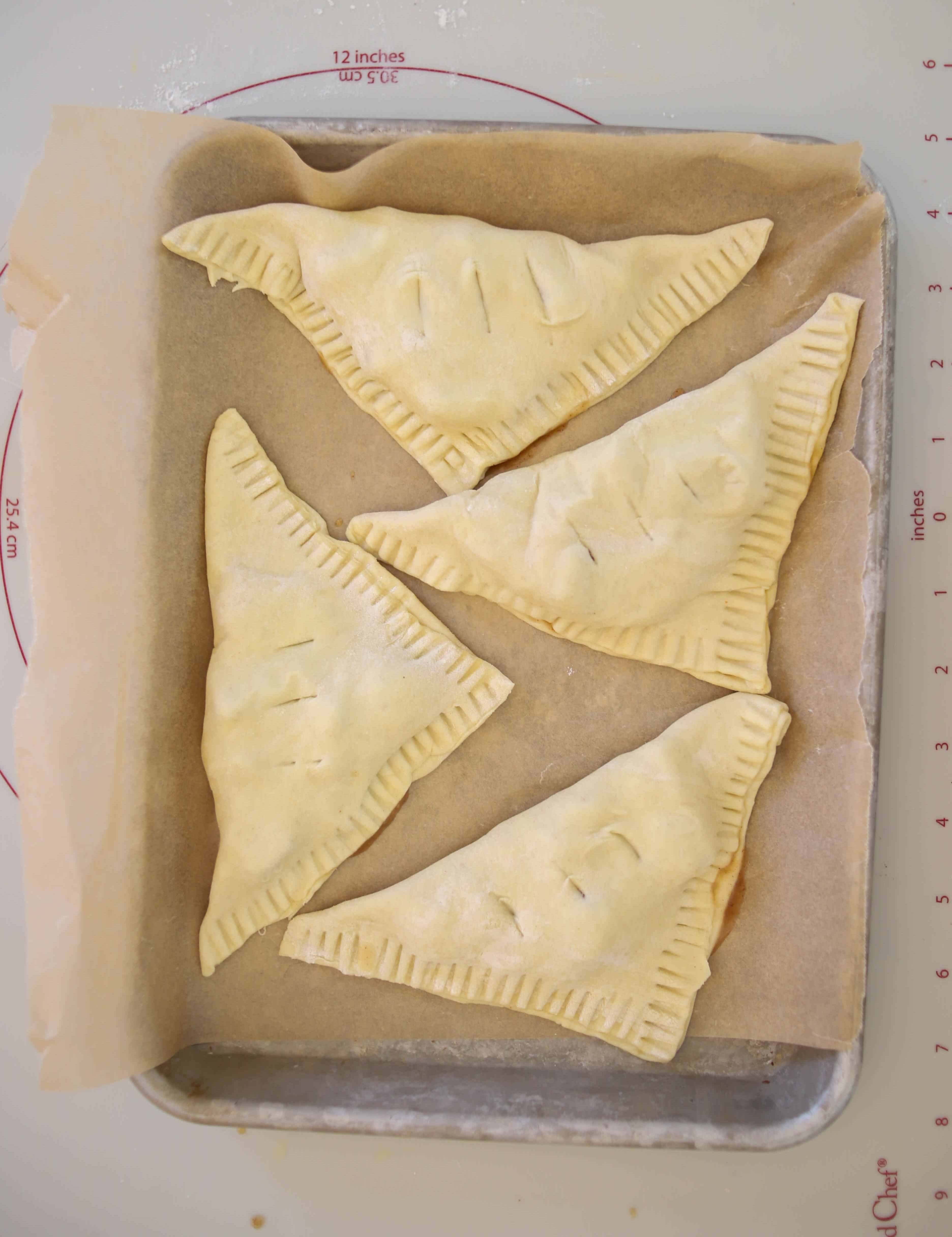 four unbaked turnovers on a baking sheet