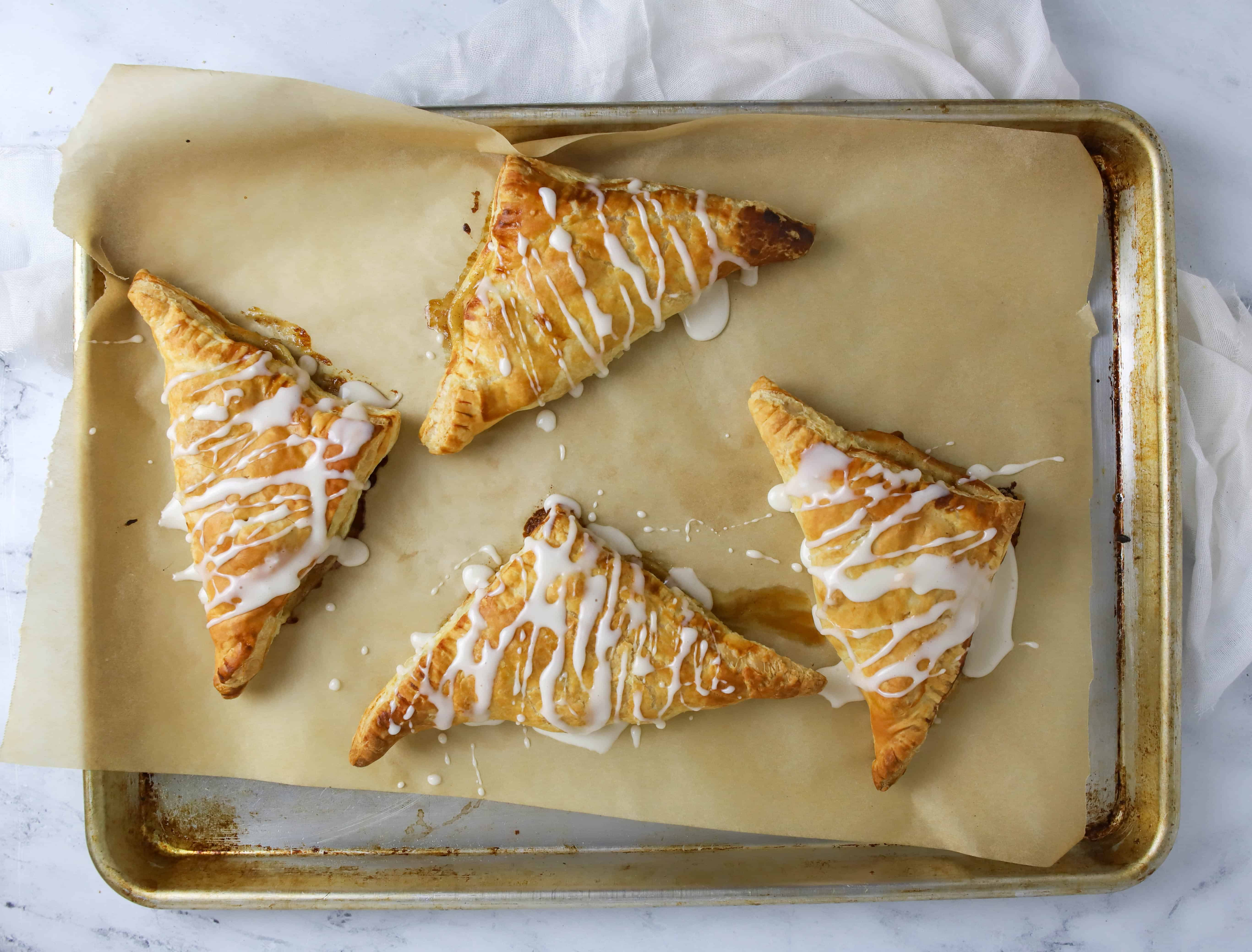four pear turnovers on a baking sheet with glaze on top