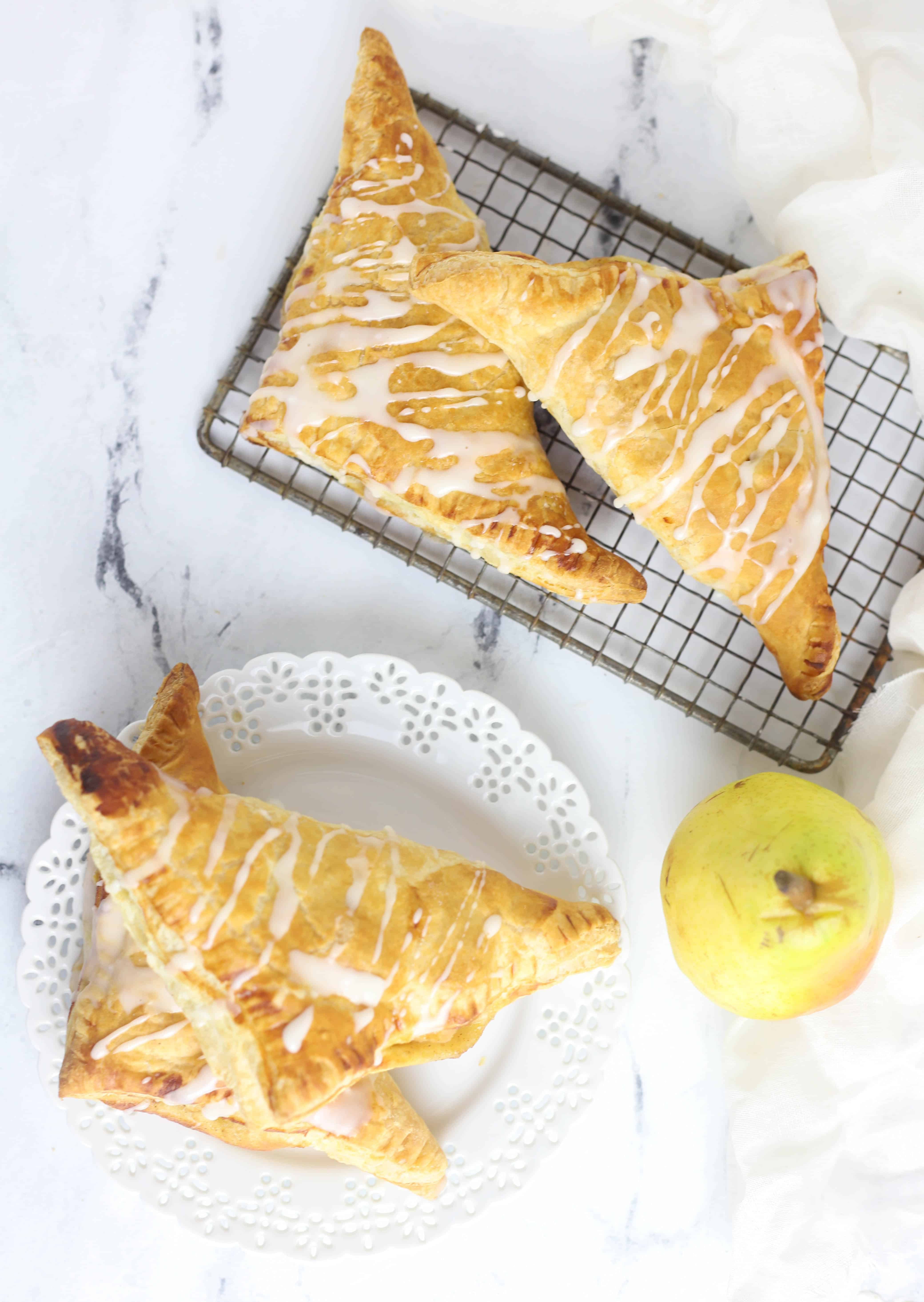four pear turnovers, two on a plate and two on a cooling rack