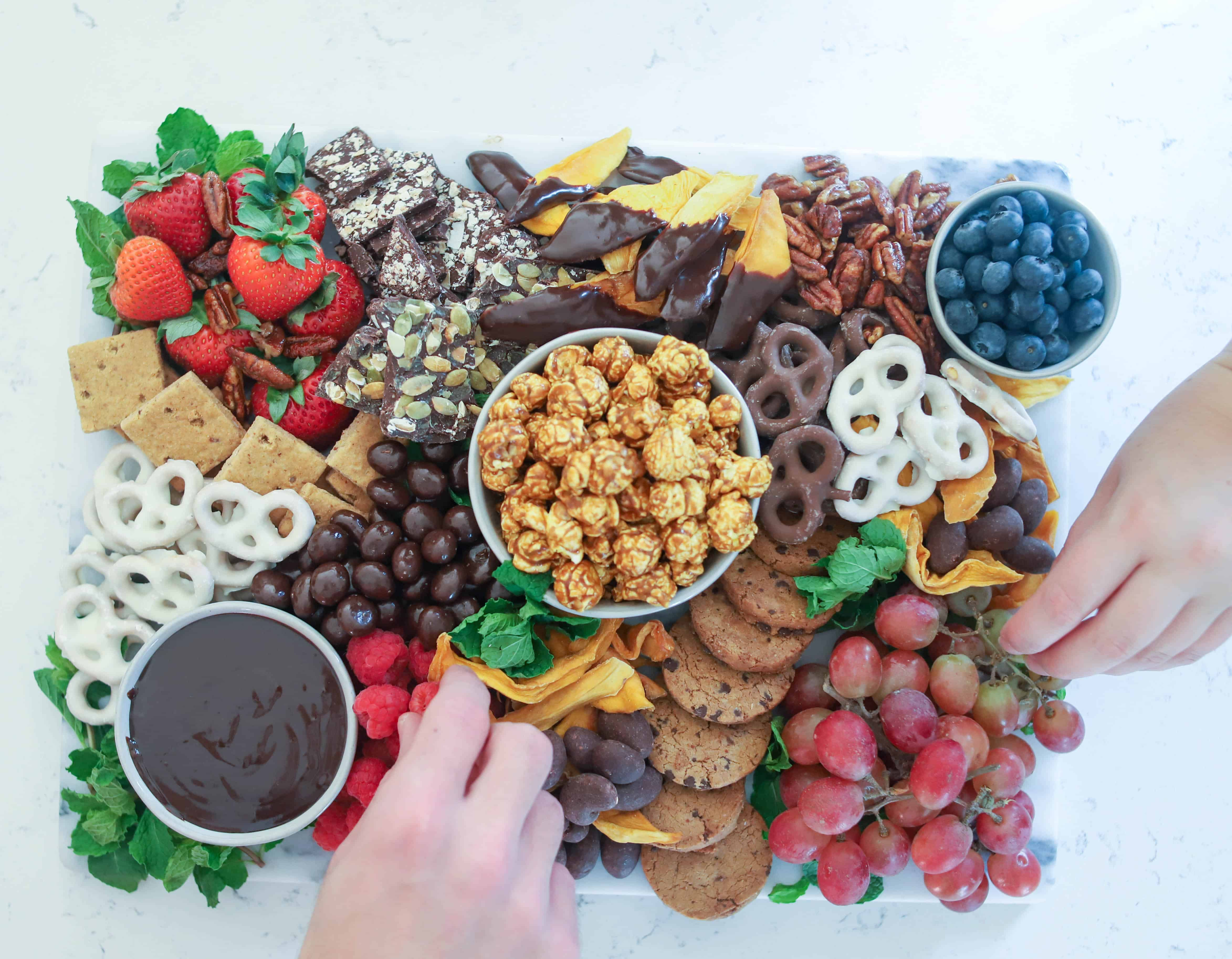 hands reaching for items on dessert board