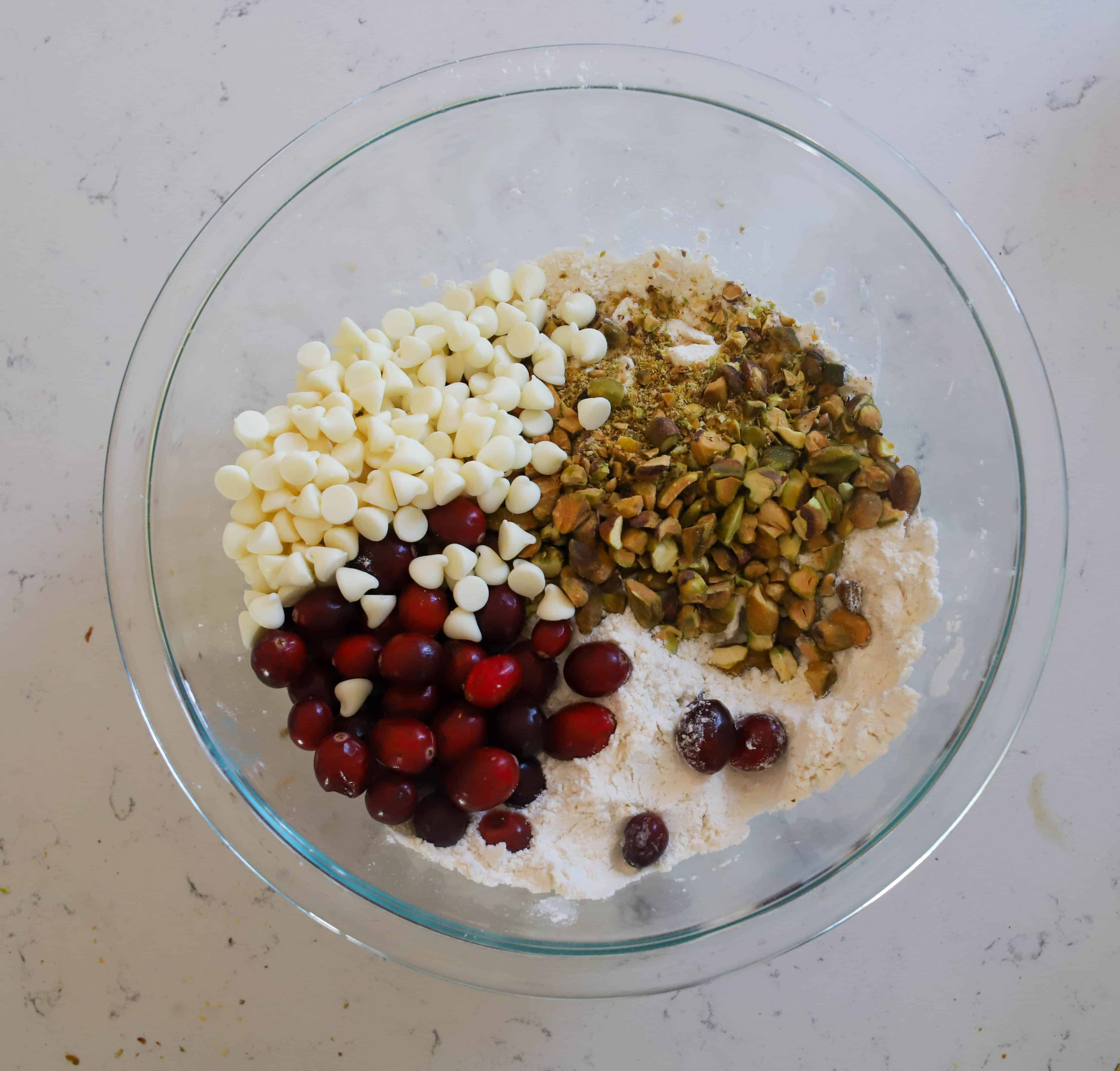 mixing bowl with white chocolate chips, pistachios, and cranberries added in