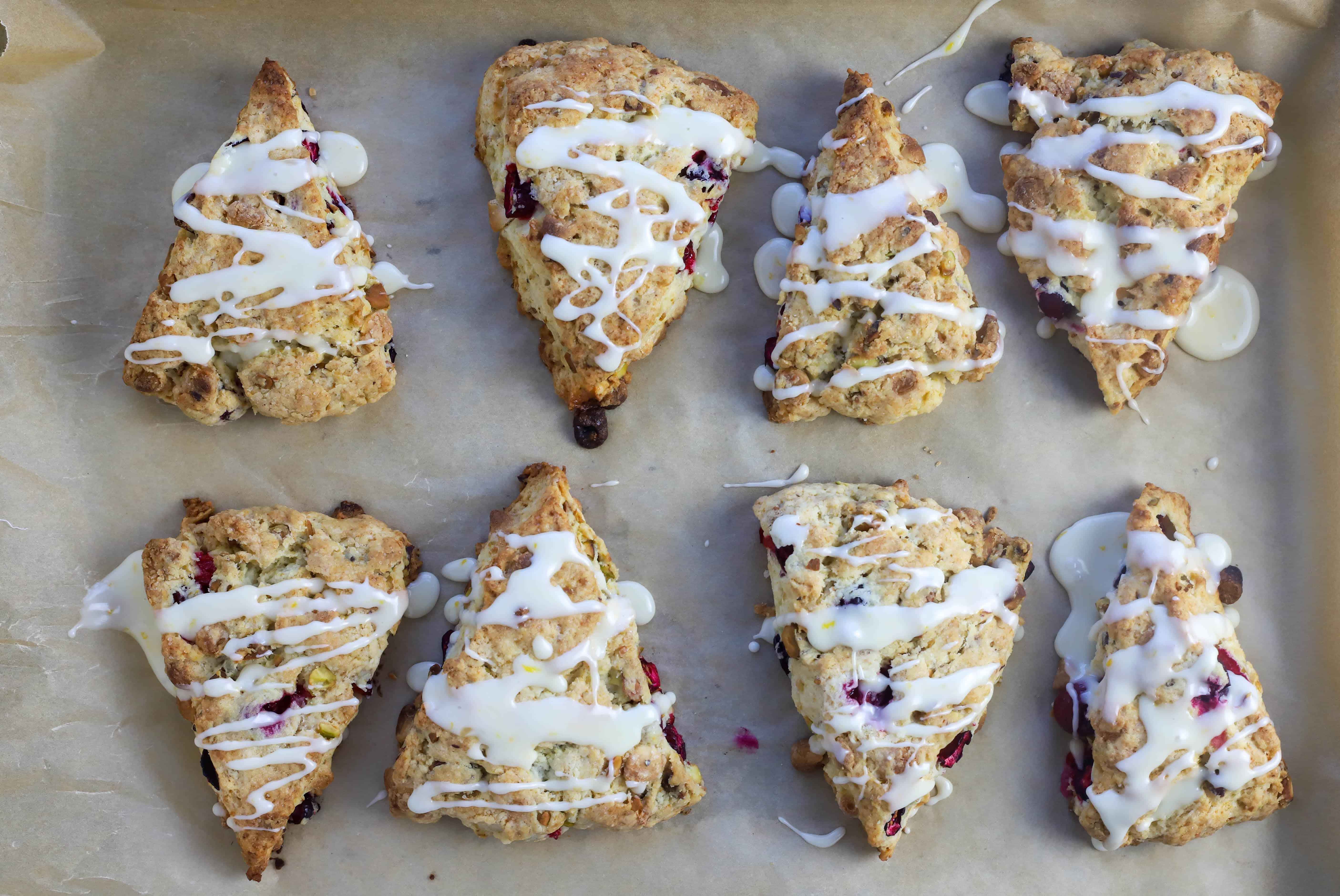 eight baked pistachio scones with orange glaze added on top