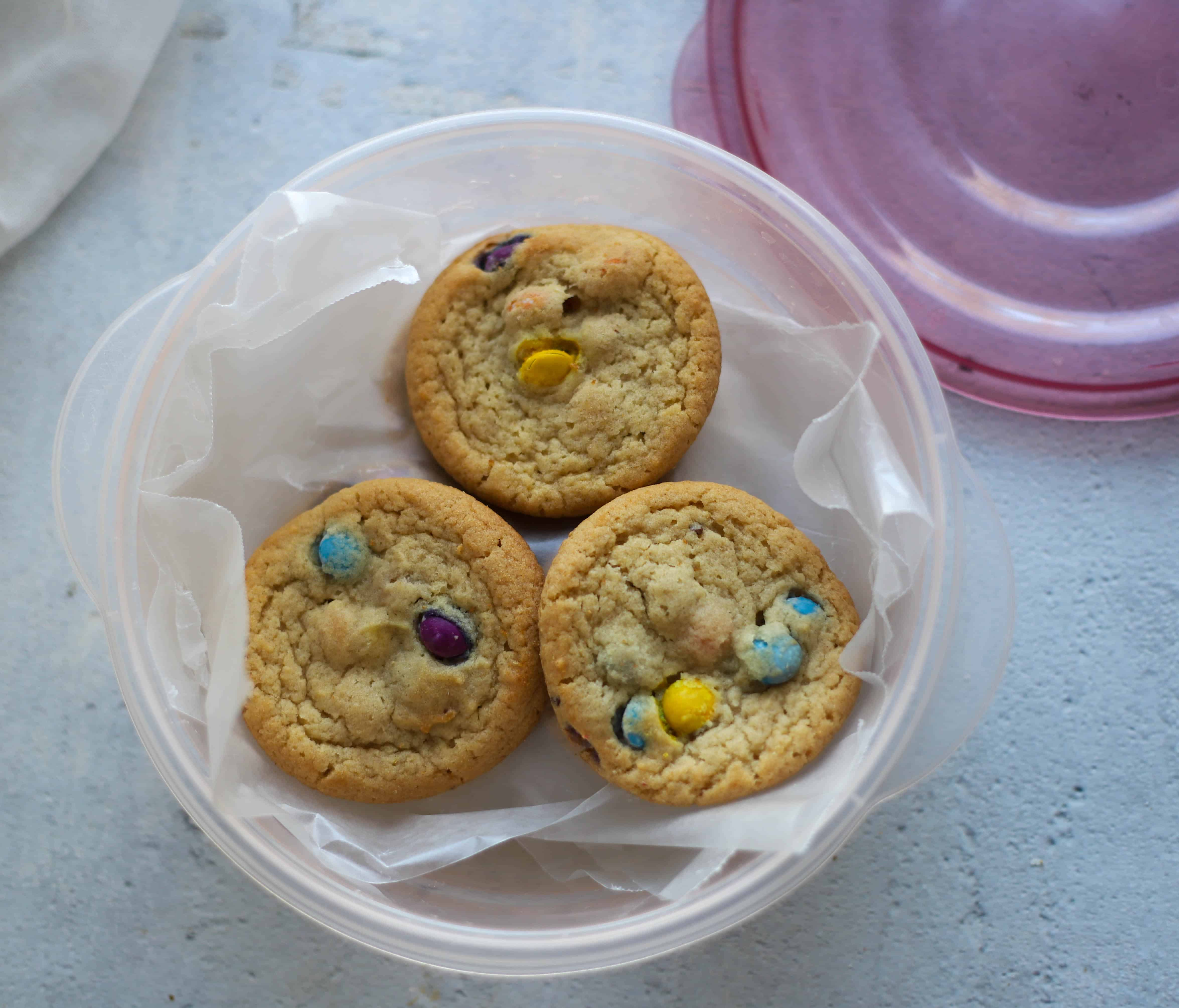 cookies layered with wax paper and stored in a plastic container