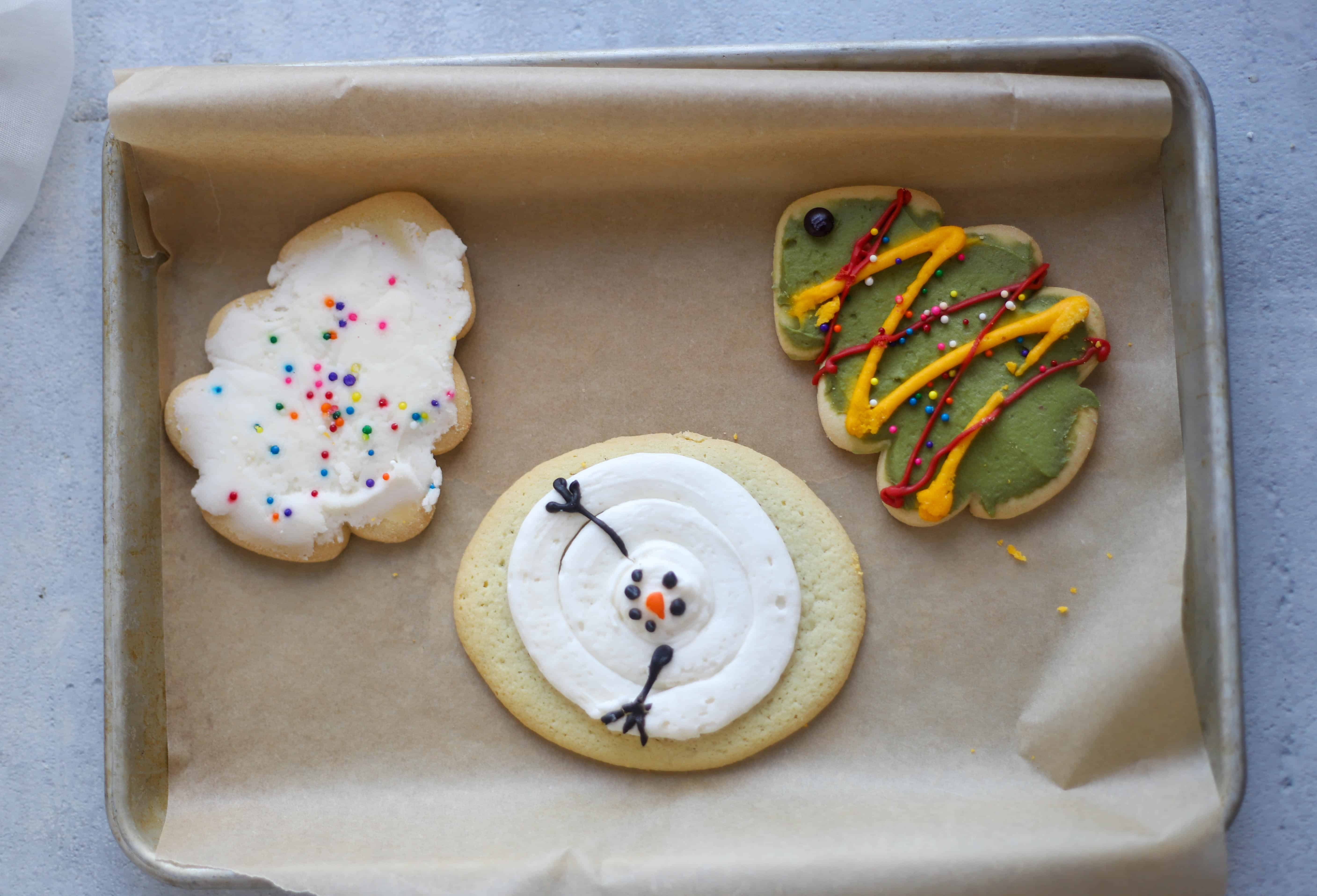 three decorated sugar cookies on a baking sheet