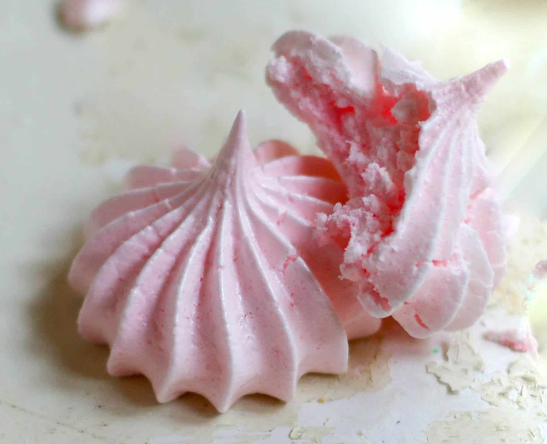 two peppermint meringues, with one having a bite taken out of it