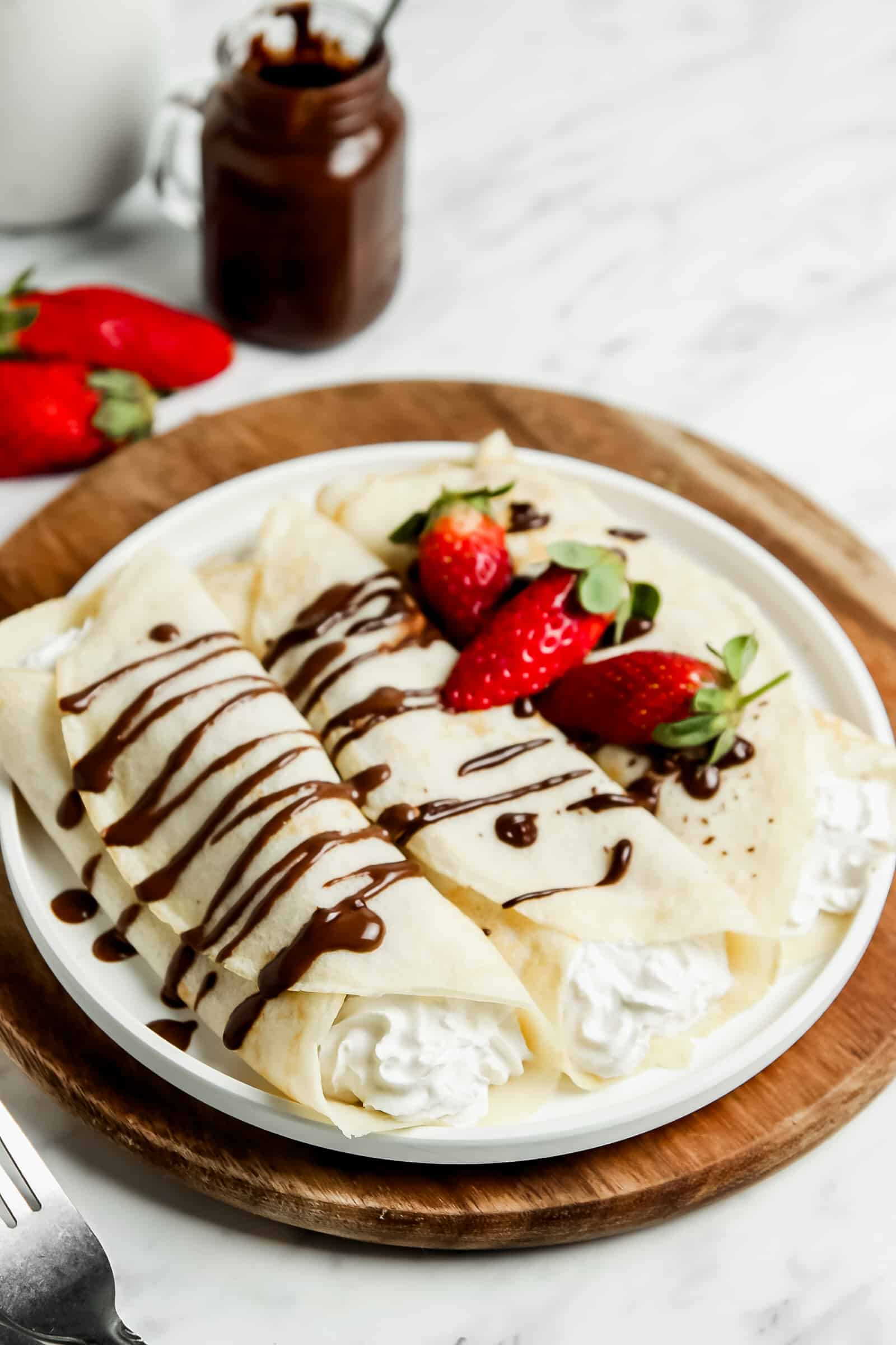 two crepes filled with whipped cream on a plate