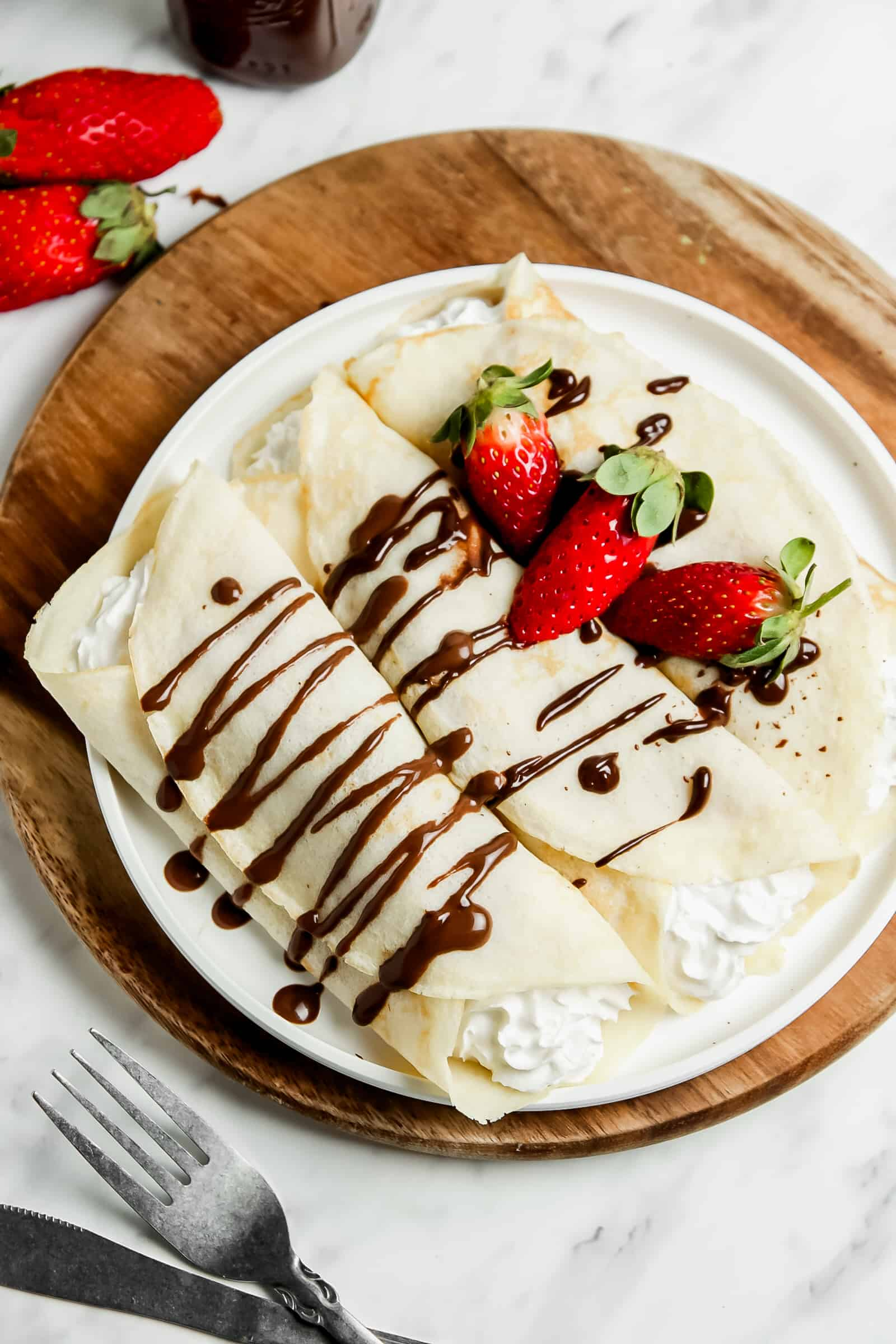 two crepes rolled and filled with whipped cream