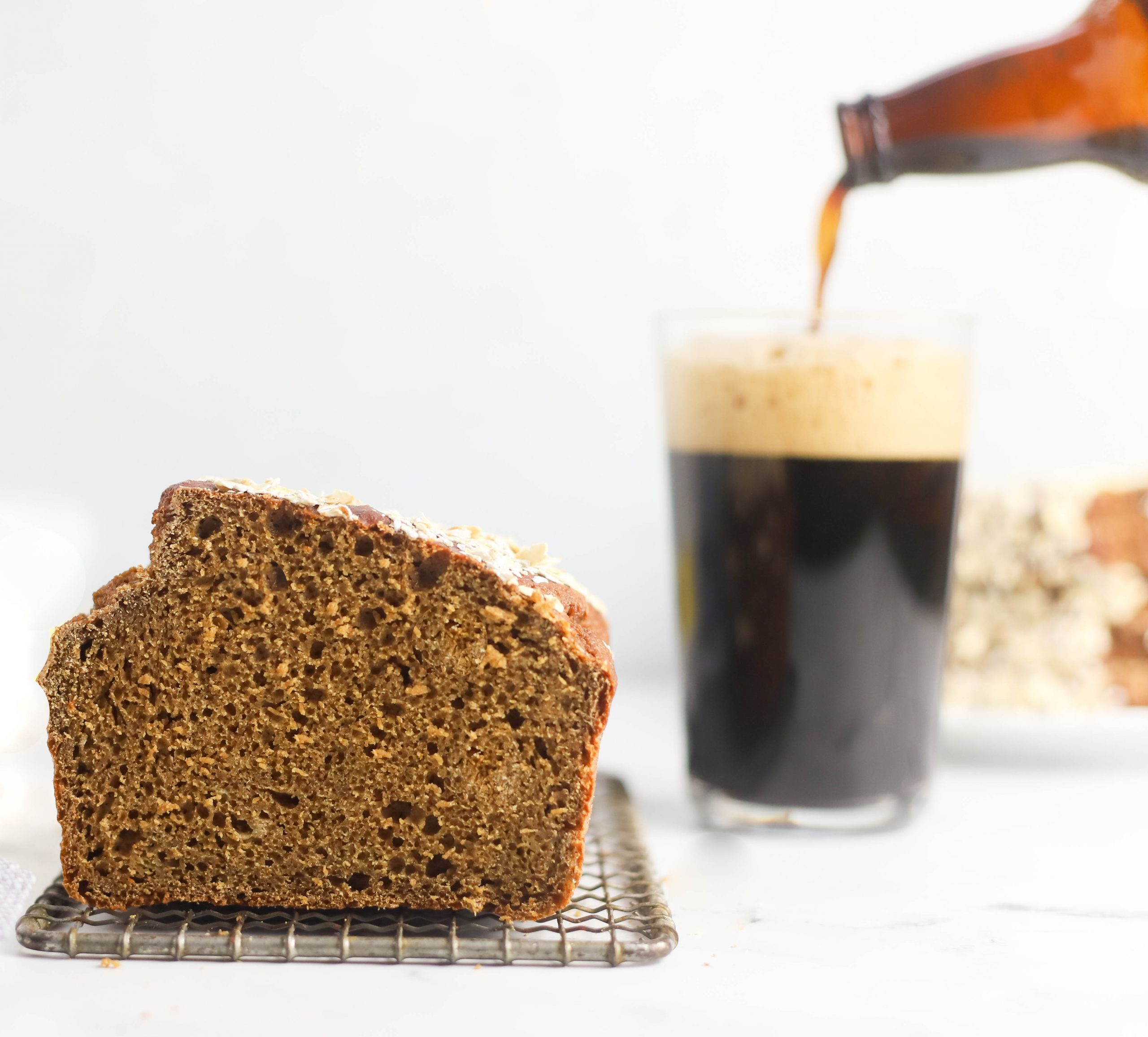 Guinness bread on a cooling rack and a Guinness beer being poured into a glass