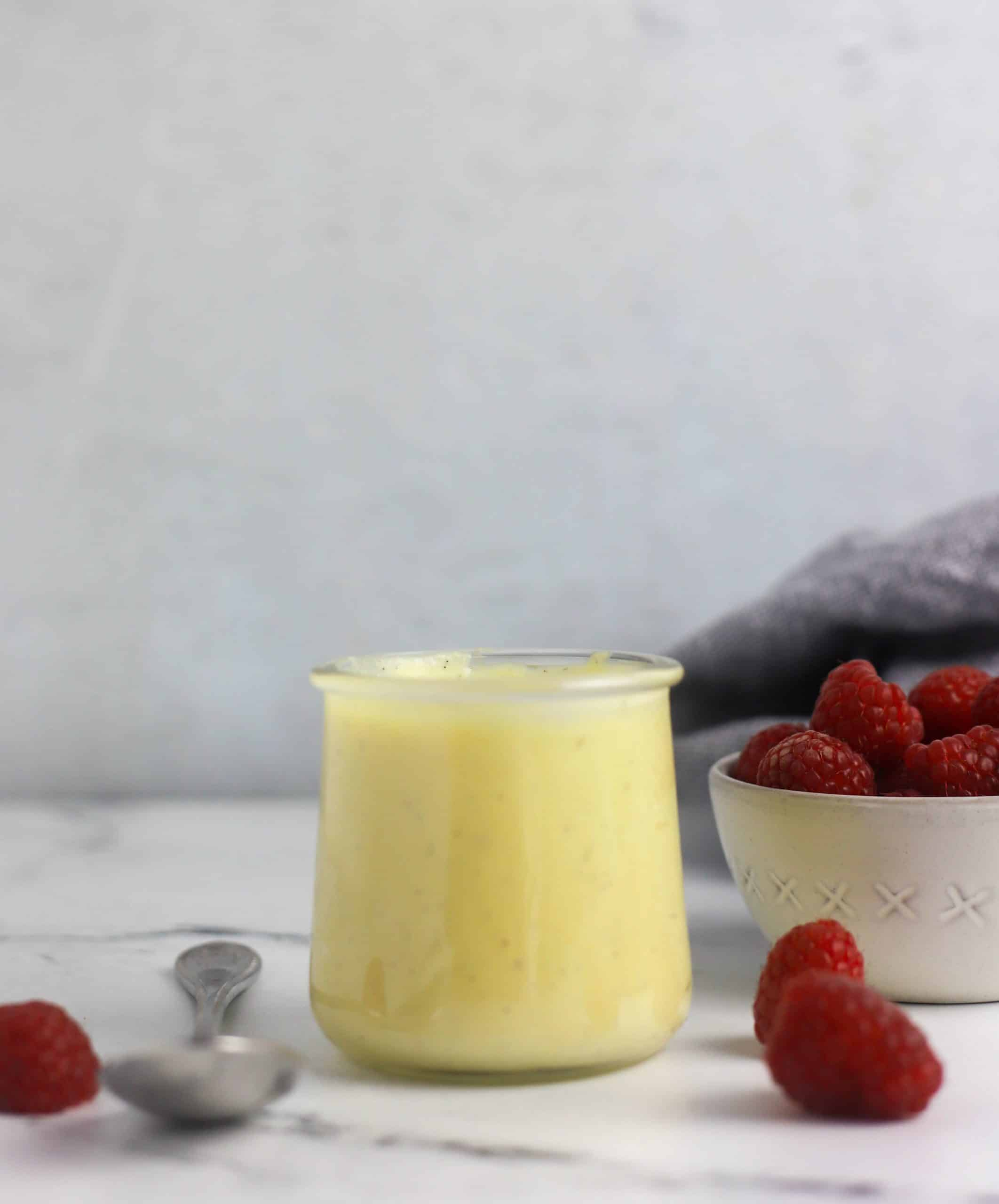 vanilla custard sauce and bowl of raspberries