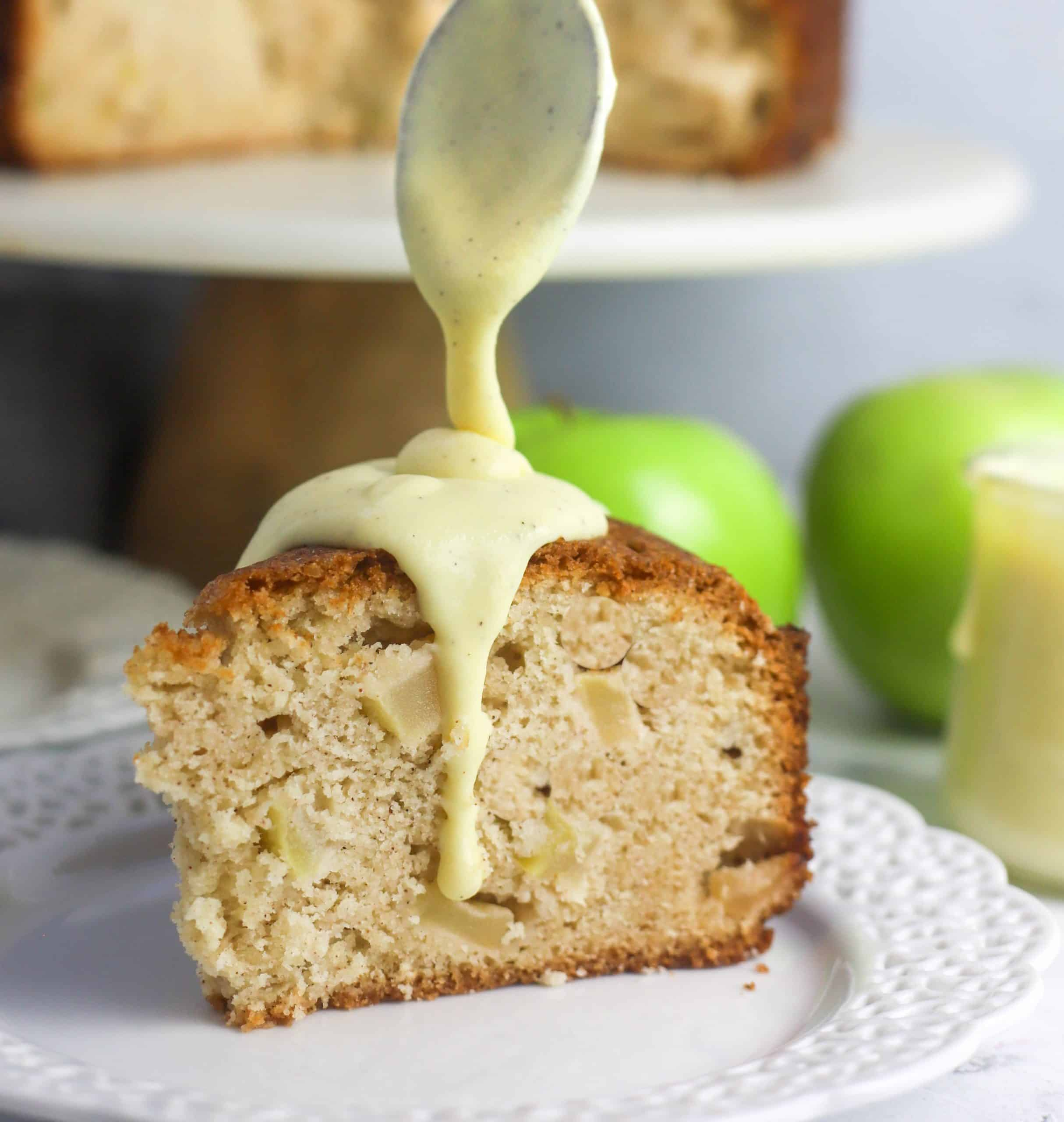 slice of Irish apple cake on a plate with custard sauce drizzled over the top