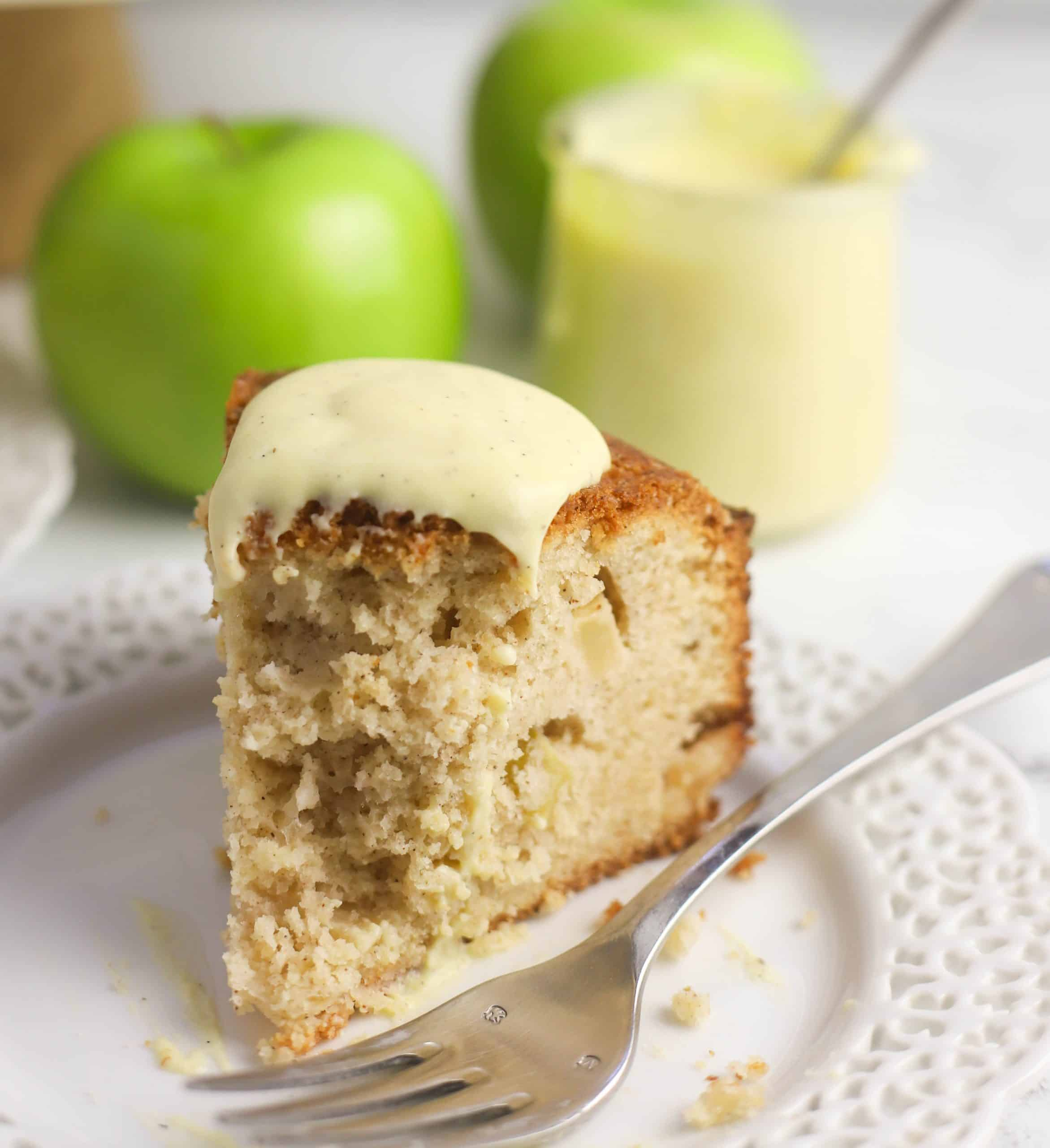 Irish apple cake with custard sauce on top on a plate with a fork