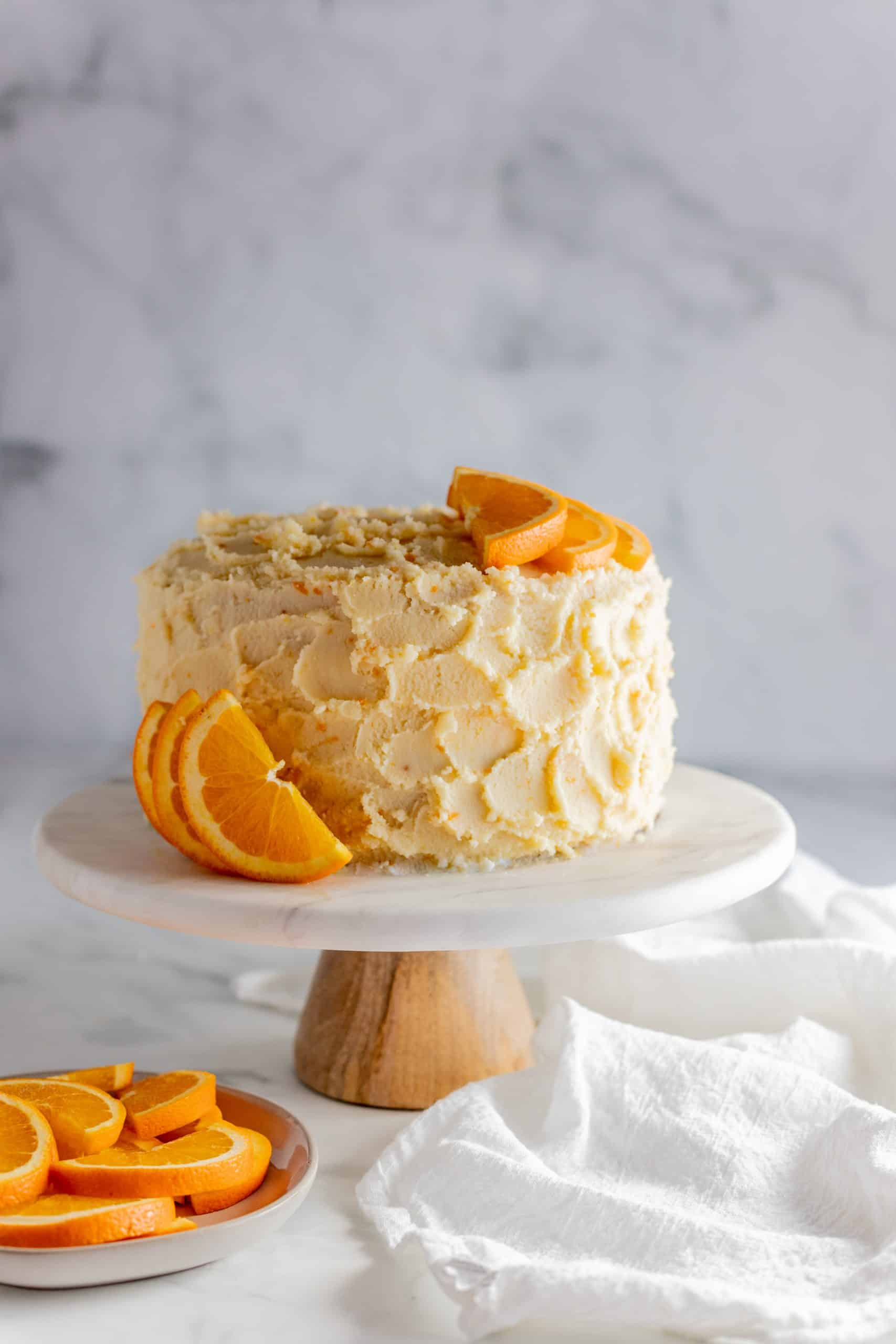 whole orange creamsicle cake on a cake stand
