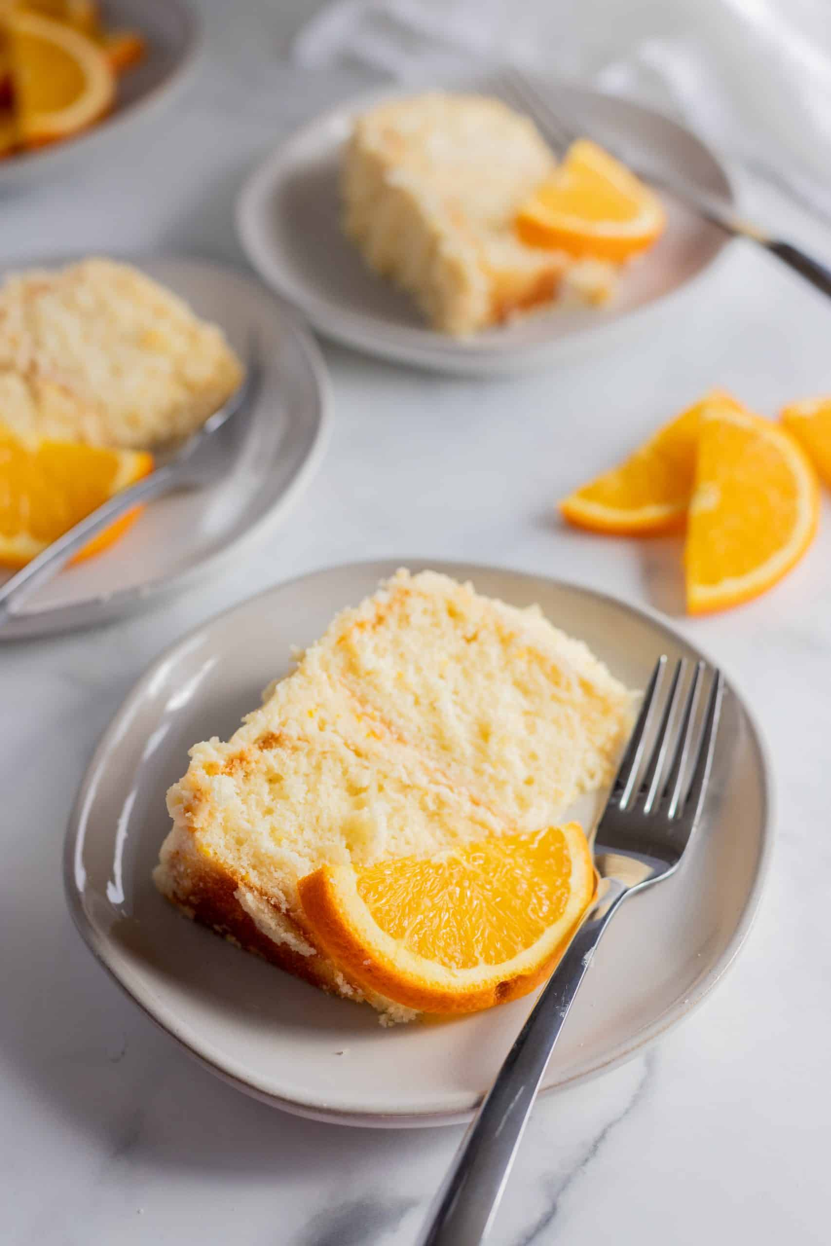 three slices of orange creamsicle cake on plates with orange slices