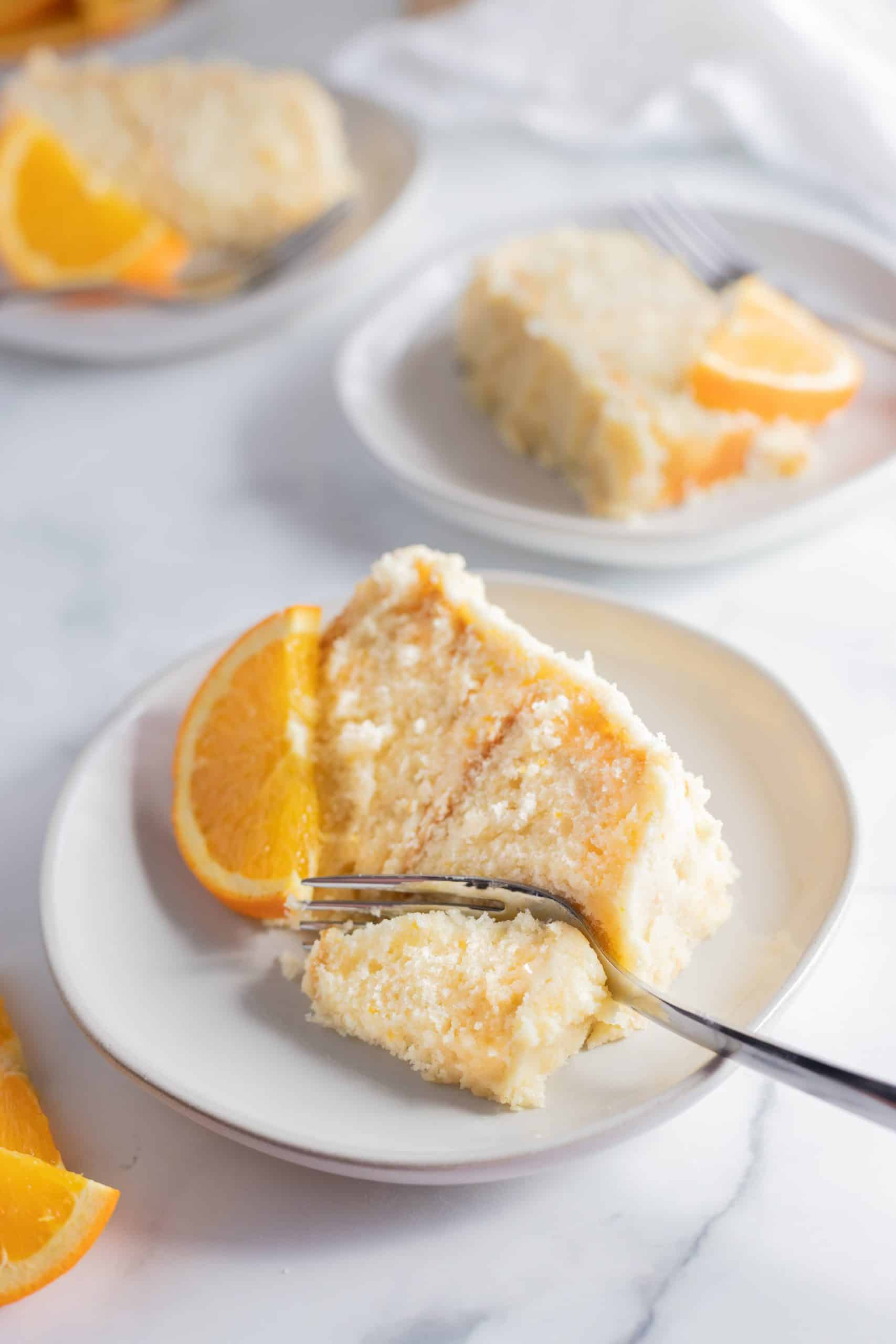 orange creamsicle cake slices on a plate with a fork
