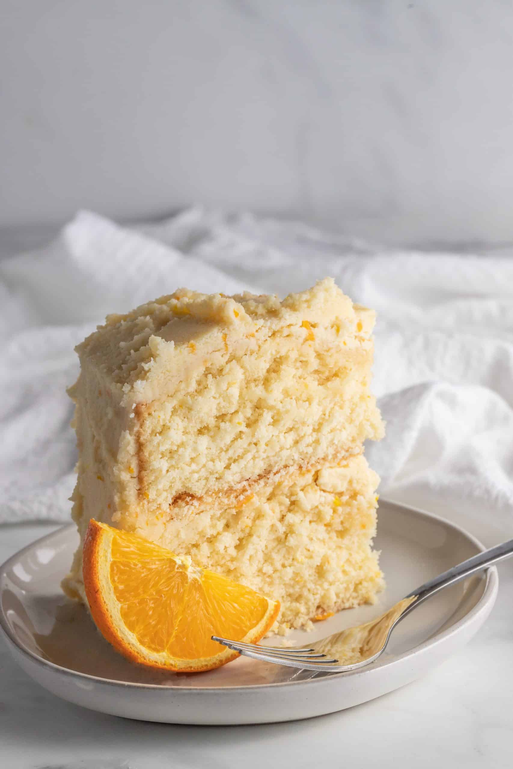 slice of orange creamsicle cake upright on a plate with a fork