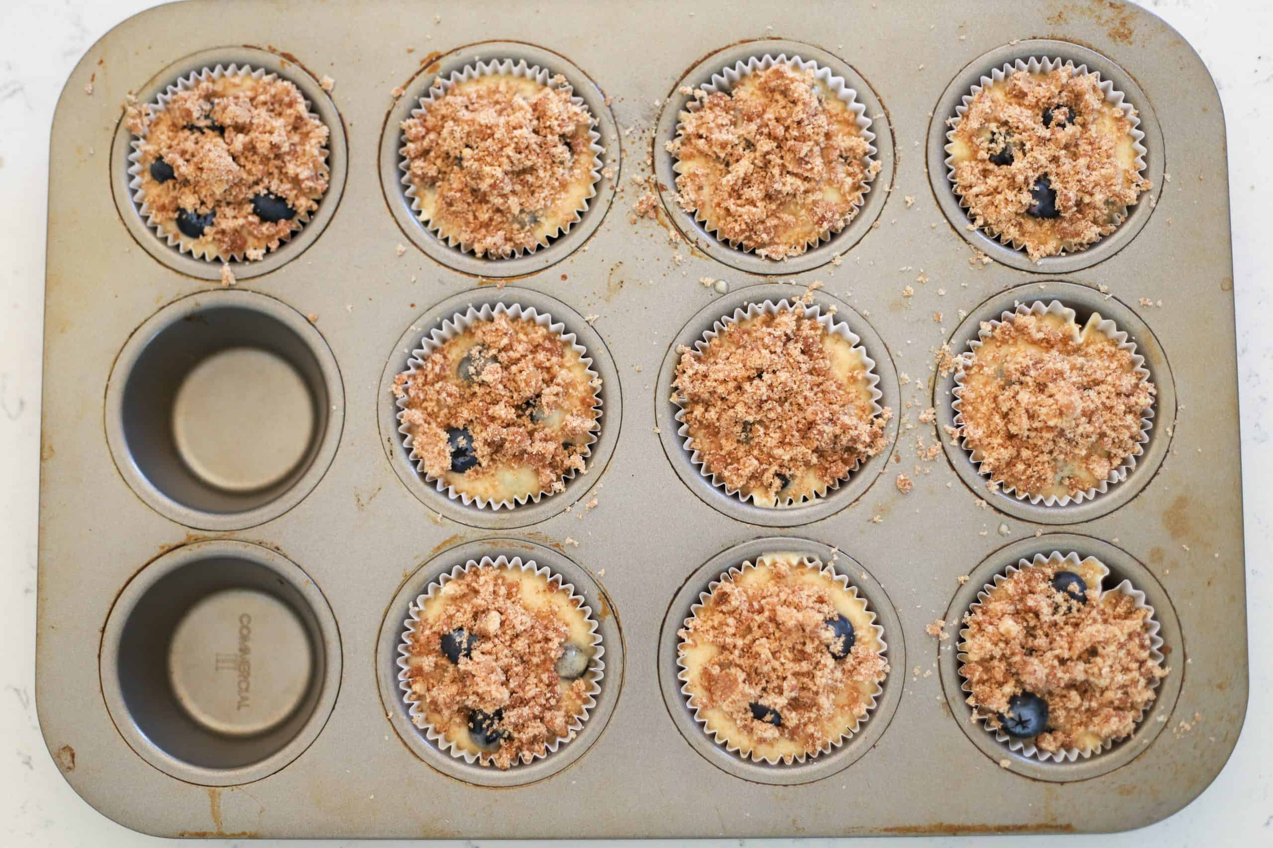 unbaked sourdough blueberry muffins with crumb topping in muffin pan