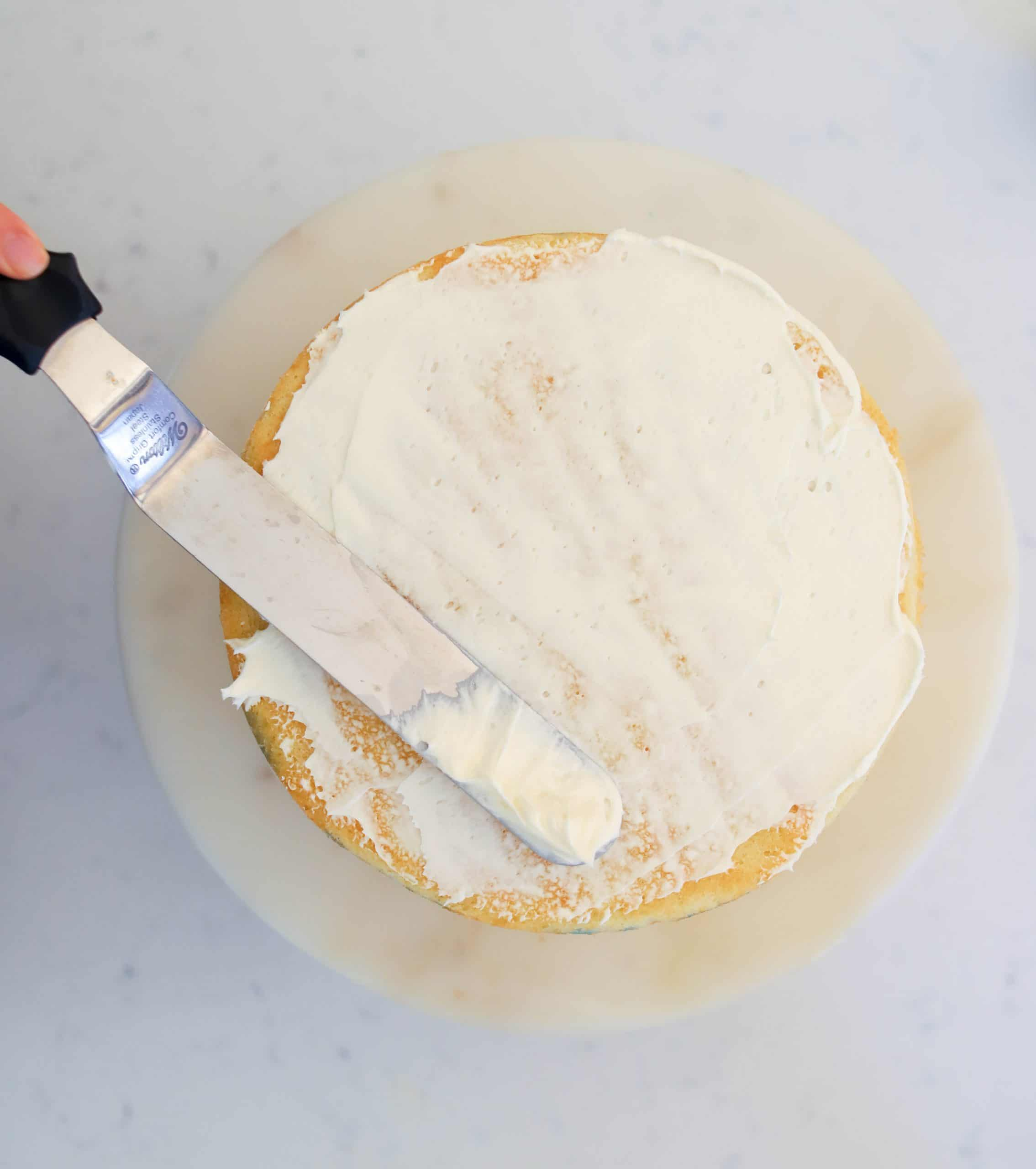 spatula crumb coating the top of a cake