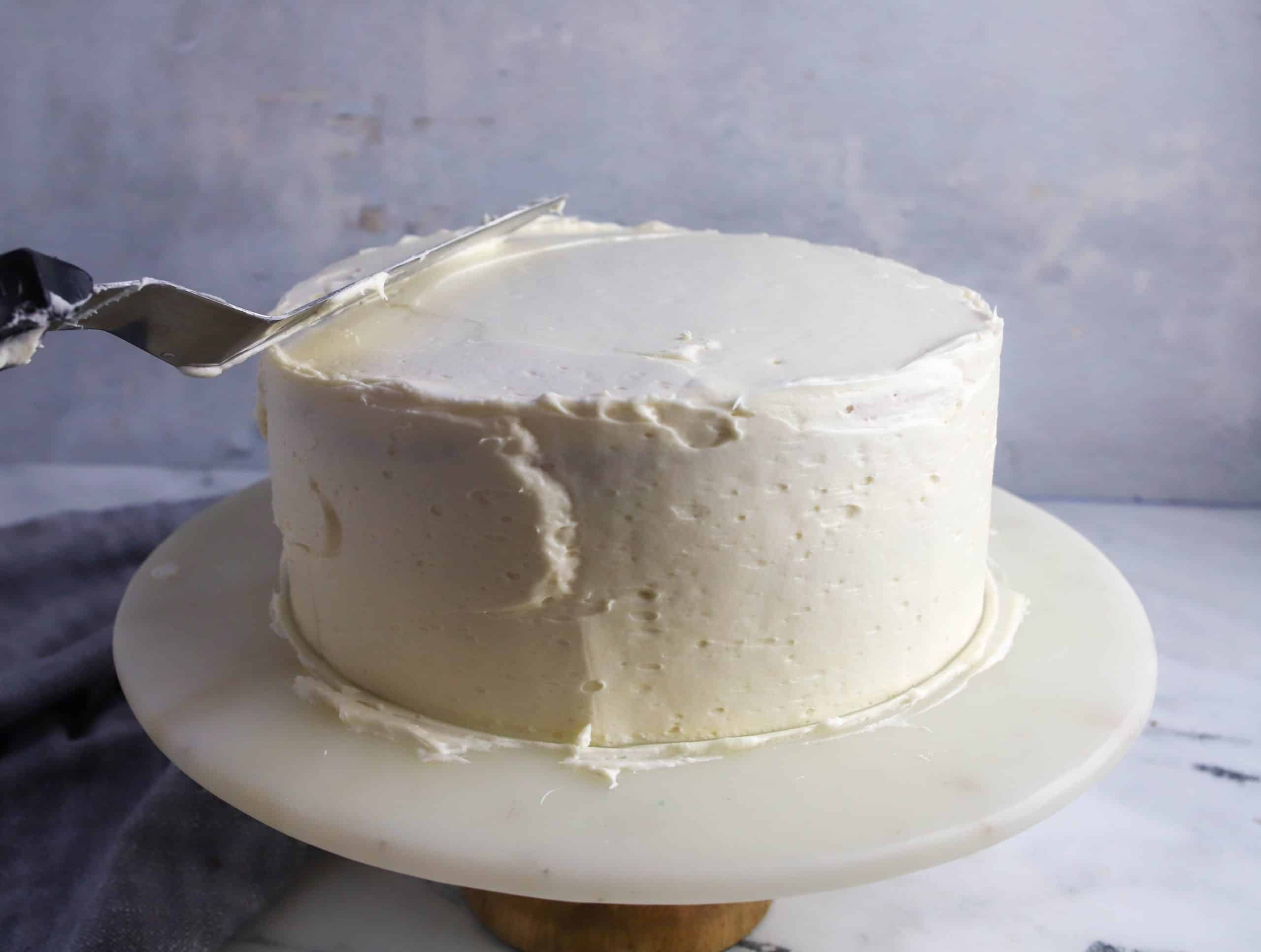 spatula smoothing top of a cake