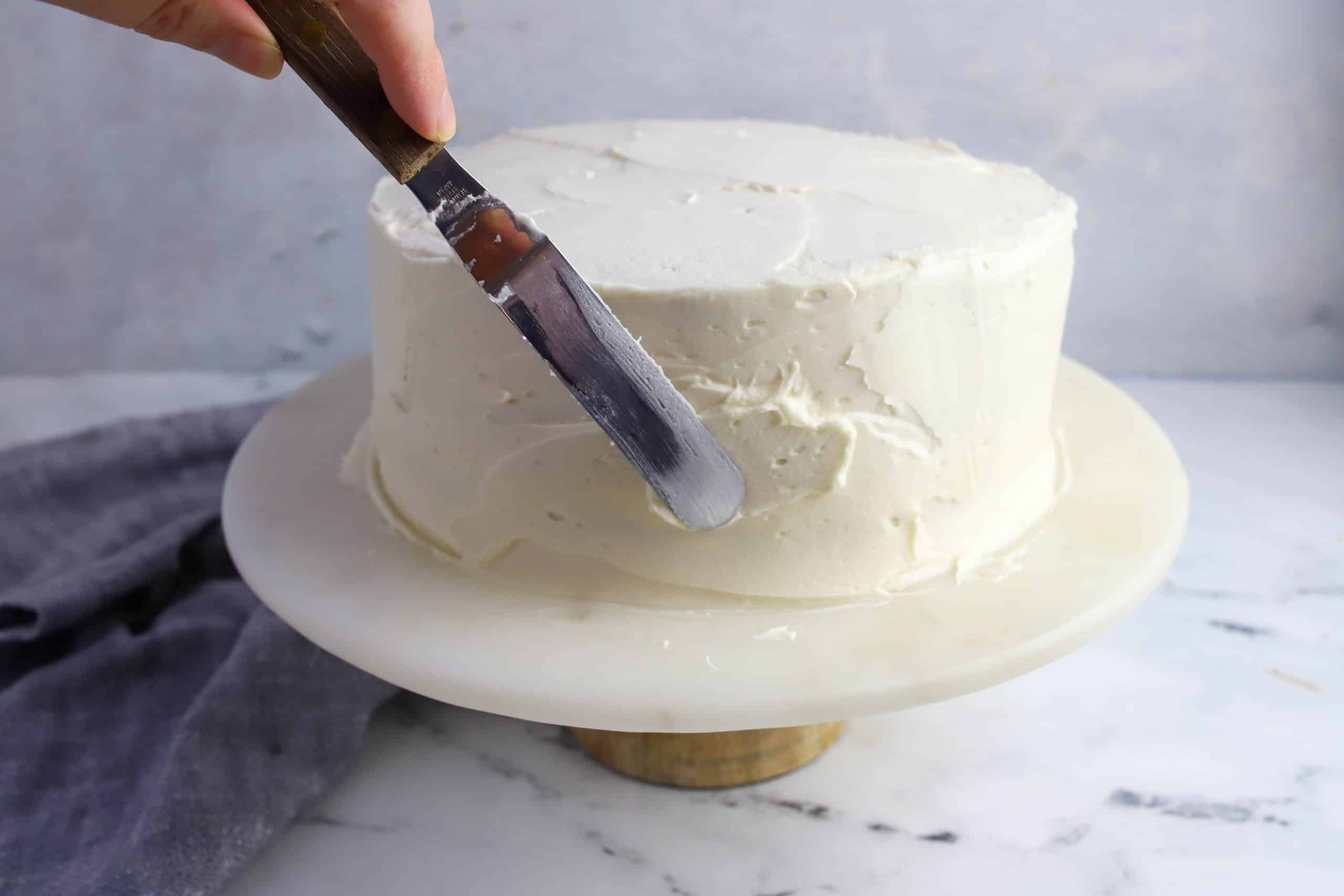 small spatula filling in gaps in frosted cake