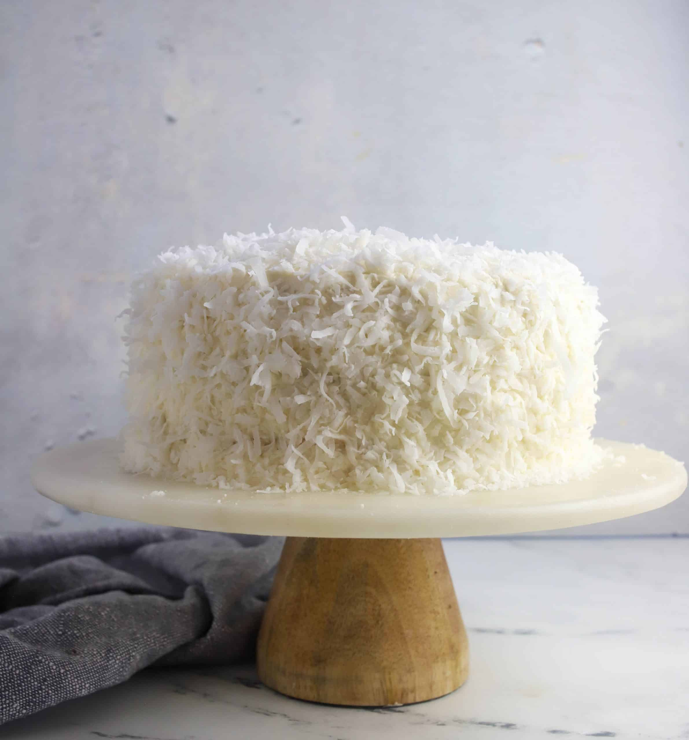 whole coconut cake on a cake stand