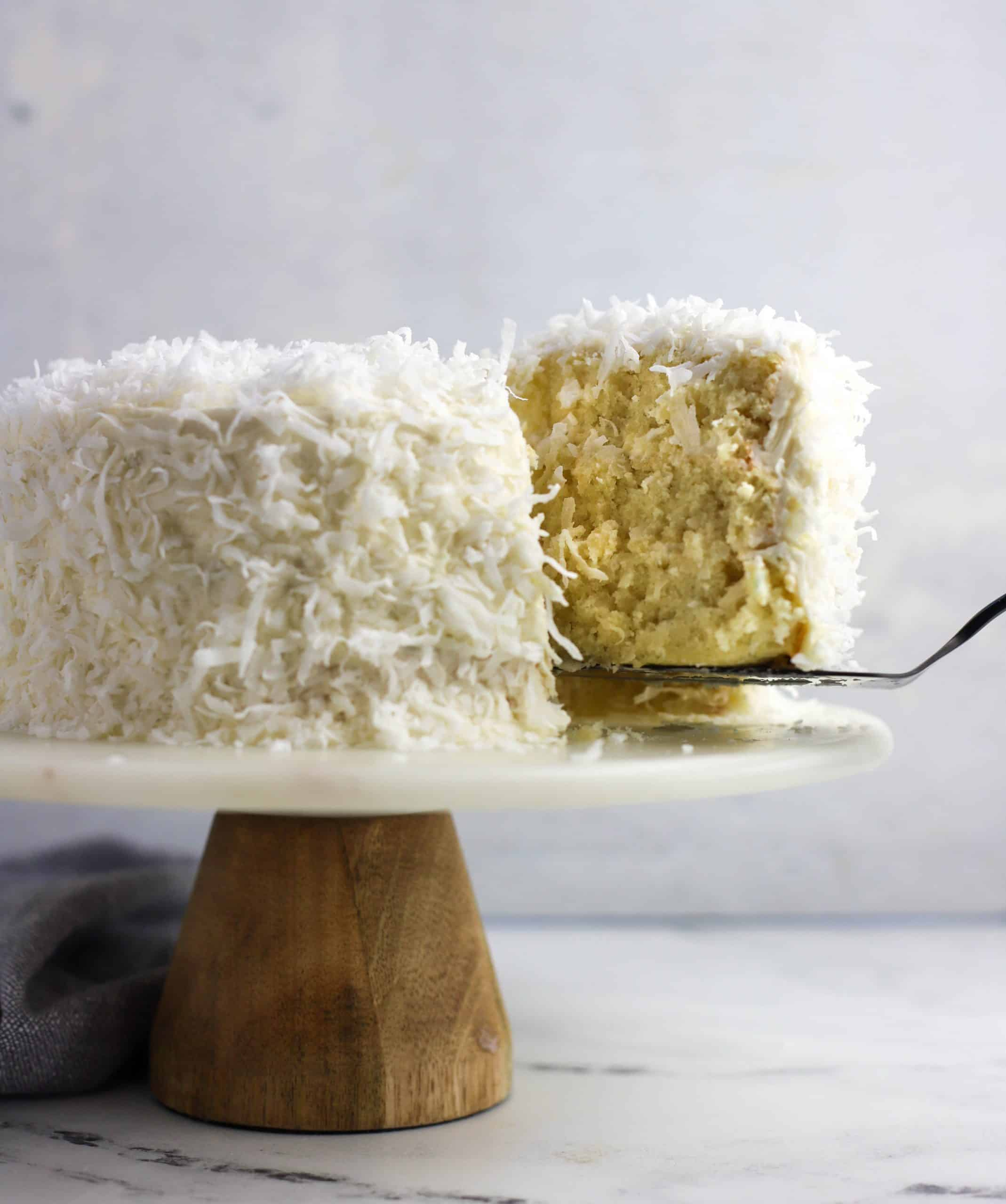 coconut cake slice being removed from the whole cake