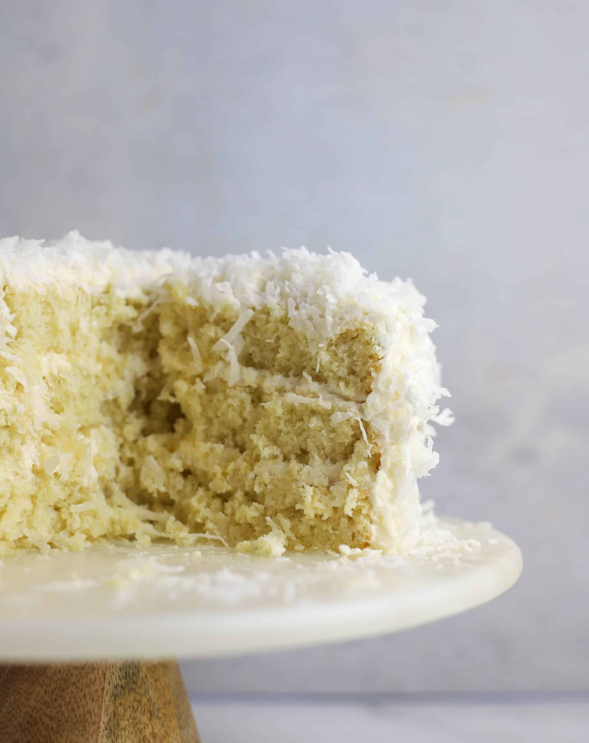 coconut layer cake cut into on a cake stand