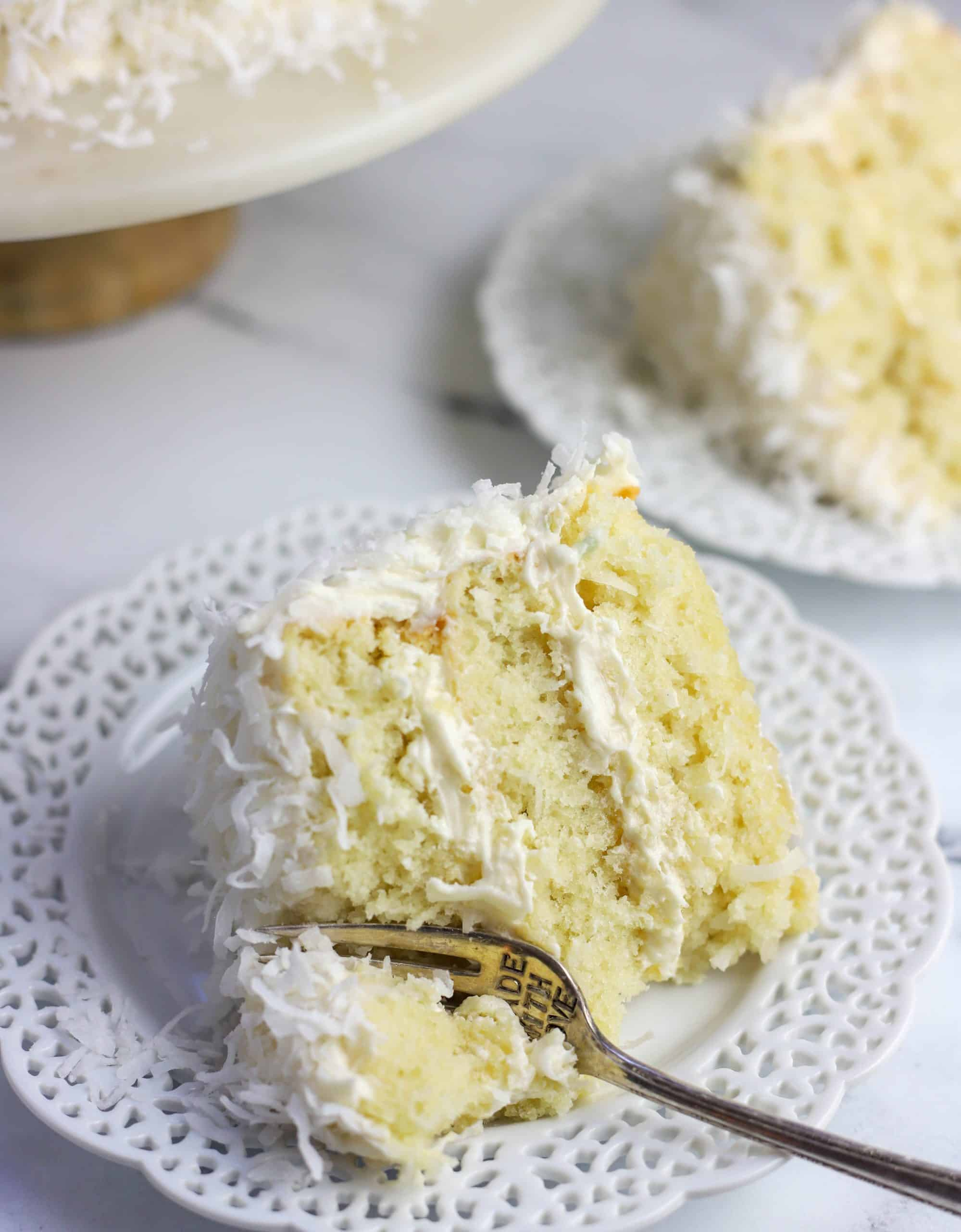 slice of coconut cake on a plate with a fork