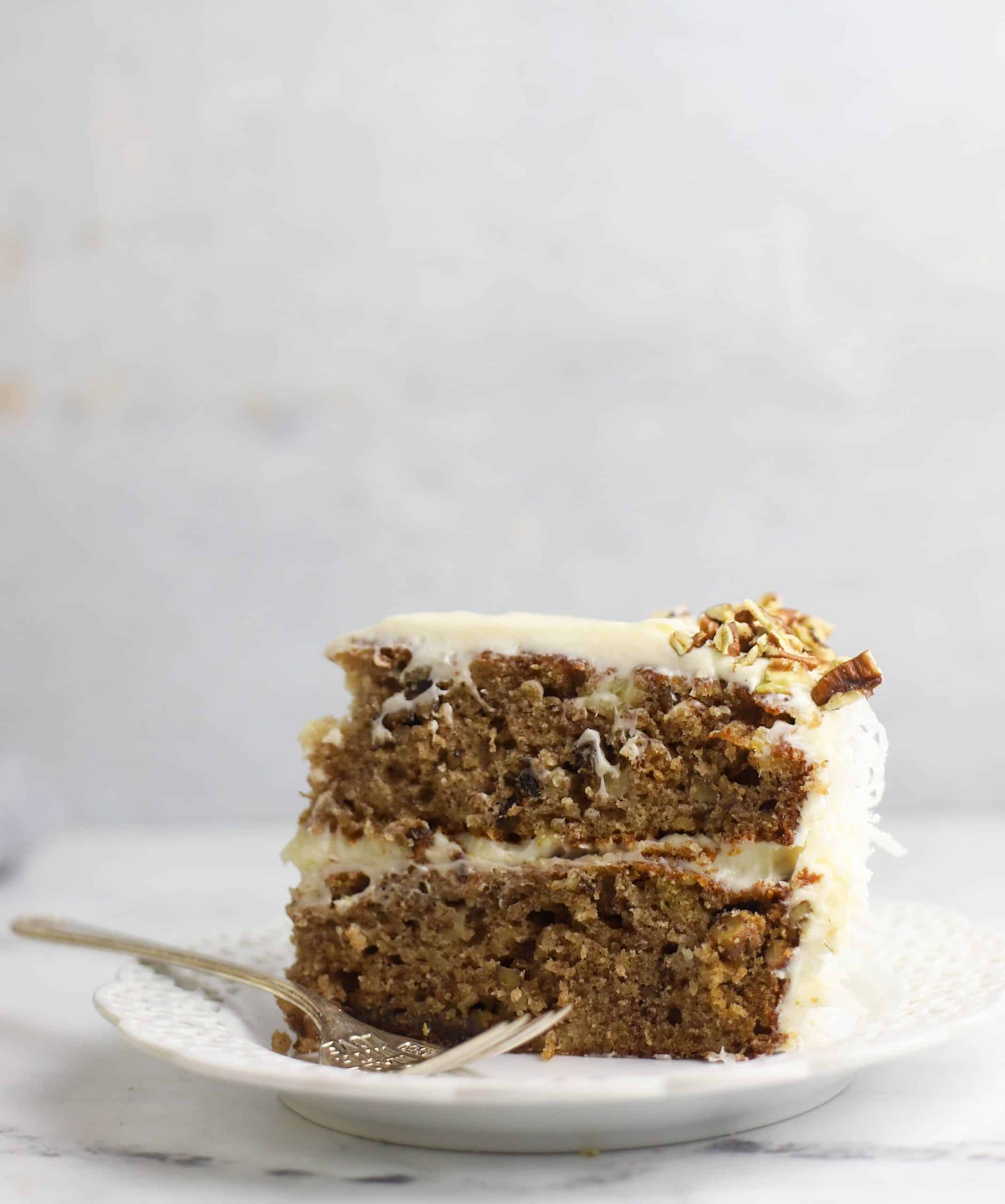 slice of hummingbird cake upright on a plate with a fork