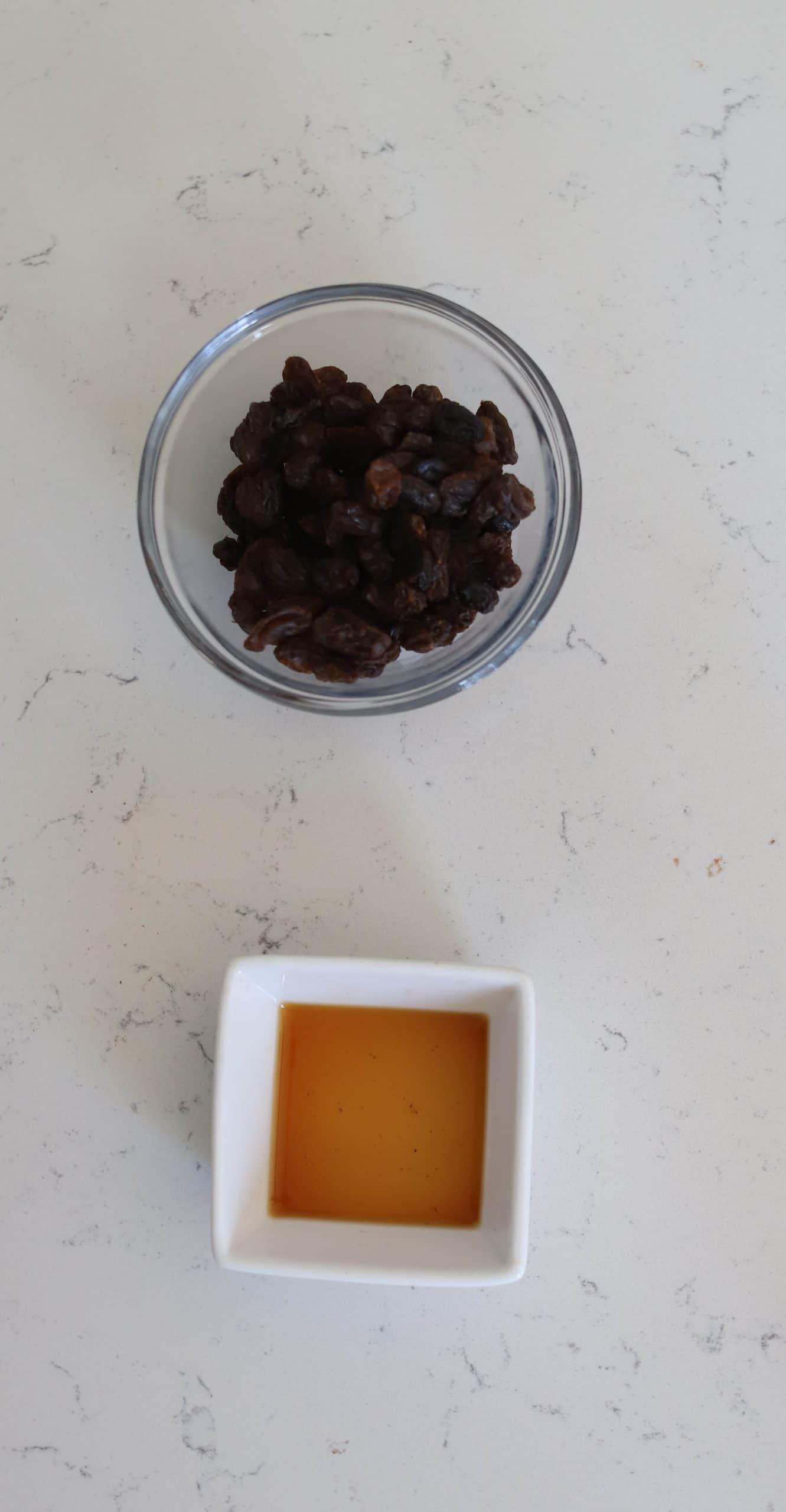 bowl of raisins and a bowl of vanilla extract