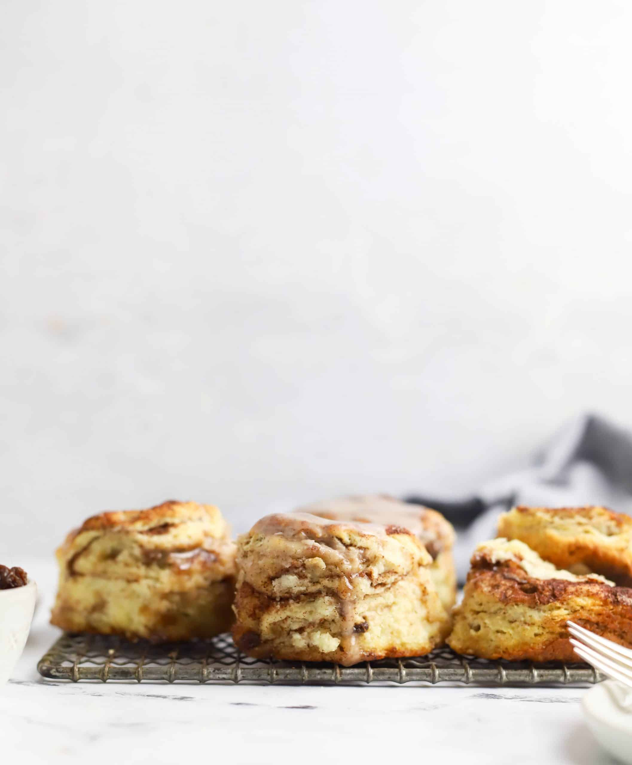 three cinnamon raisin biscuits on a cooling rack
