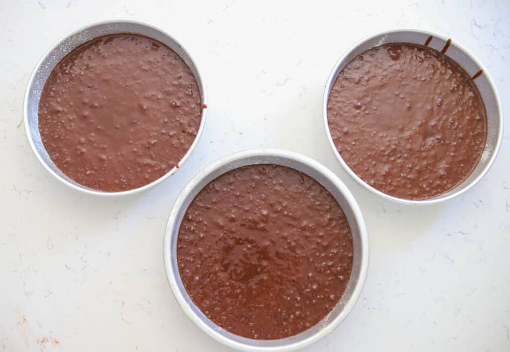 three cake pans with unbaked cake batter