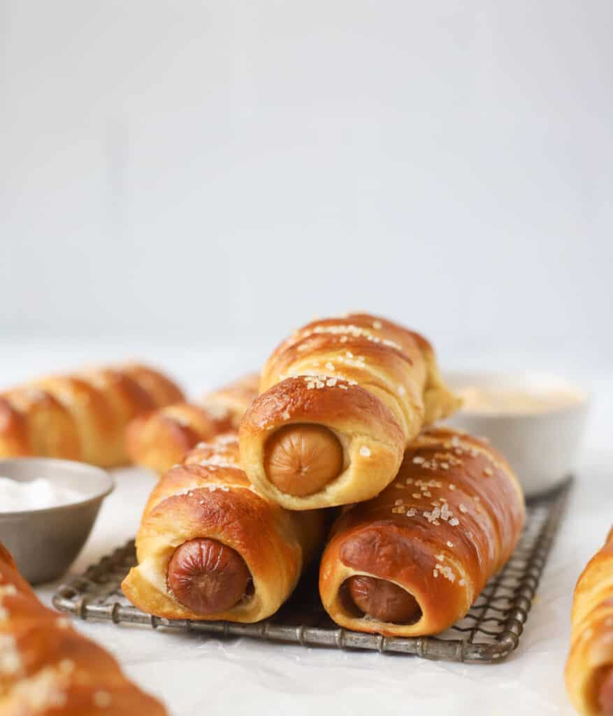 three pretzel dogs stacked on a wire cooling rack