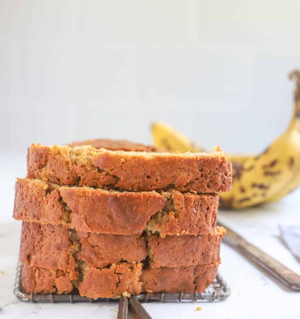 four slices of sourdough banana bread stacked on a wire rack