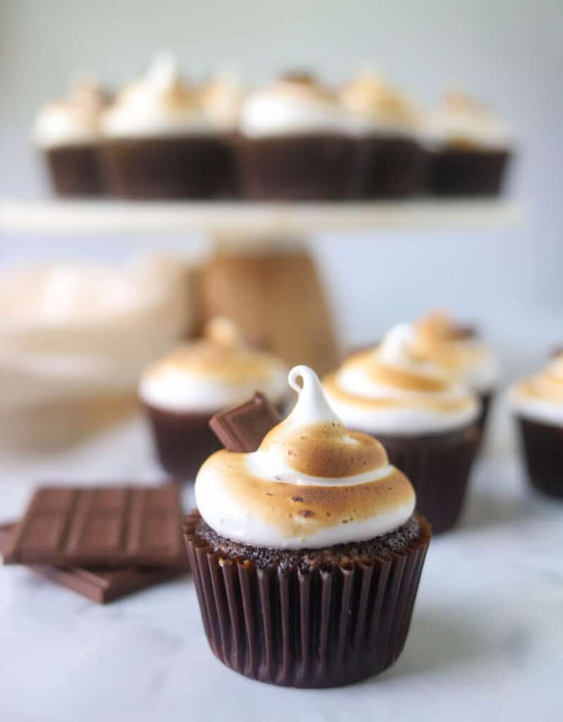 S'mores cupcake with more cupcakes in the background on a cake stand