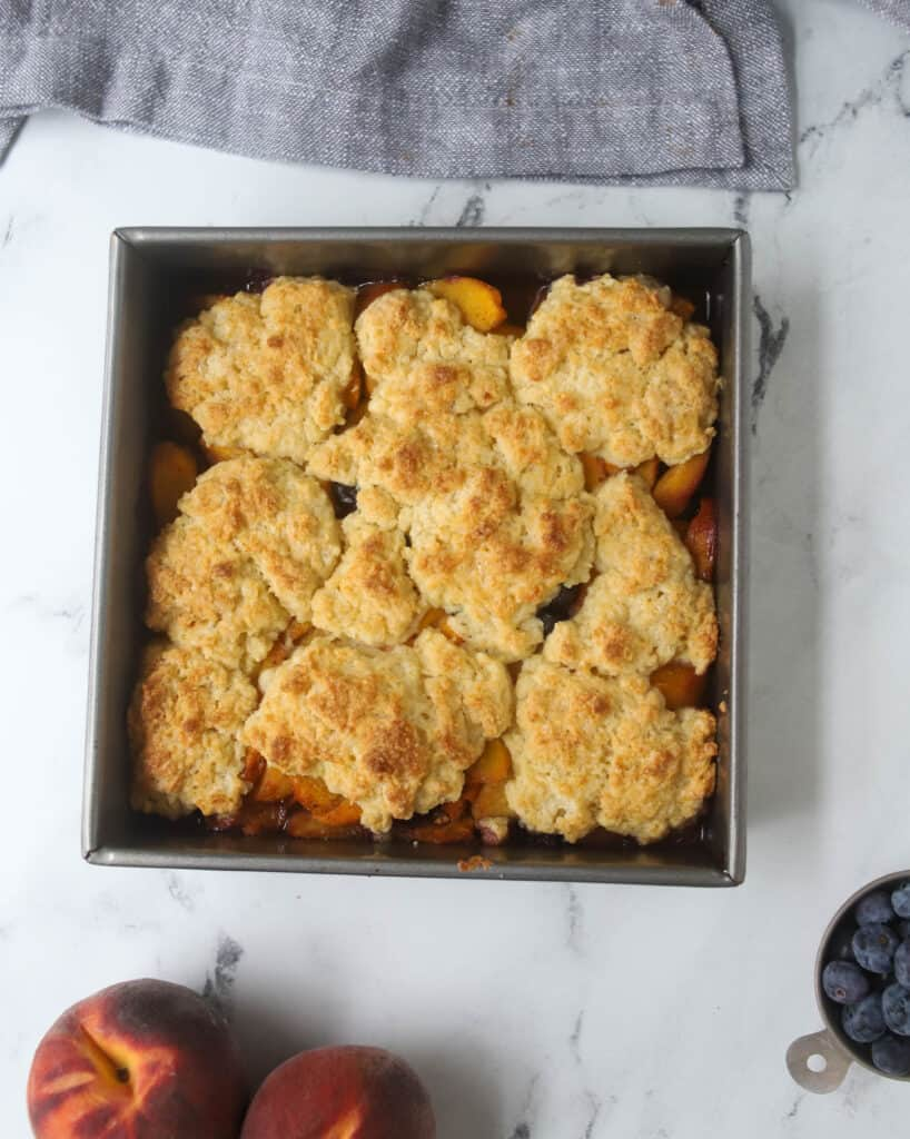 baked peach blueberry cobbler in an 8x8 pan