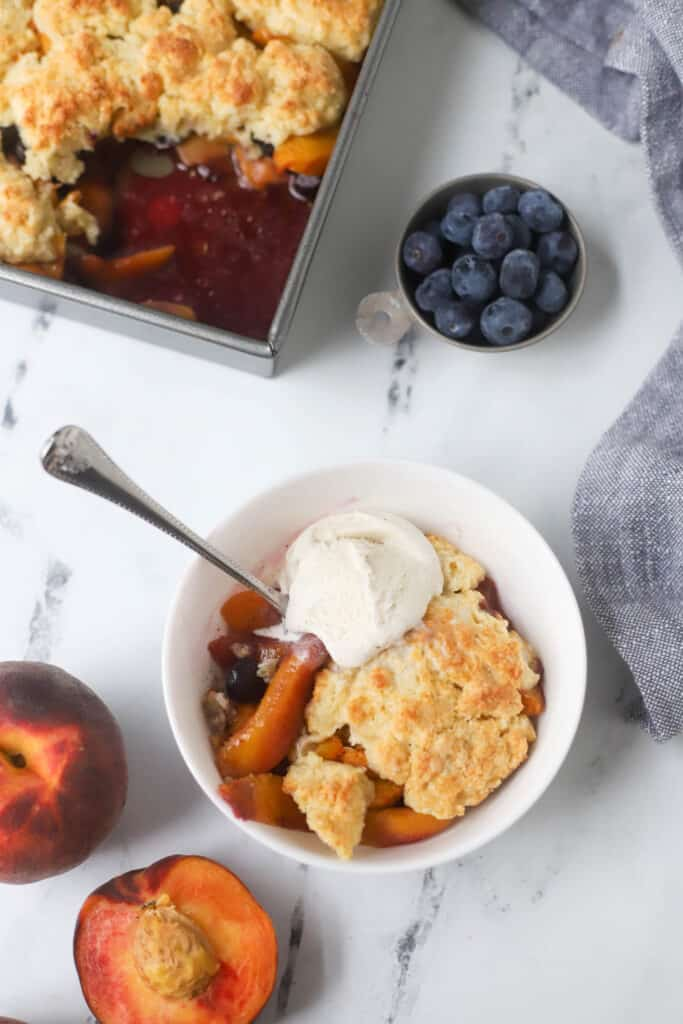 bowl of peach blueberry cobbler topped with ice-cream