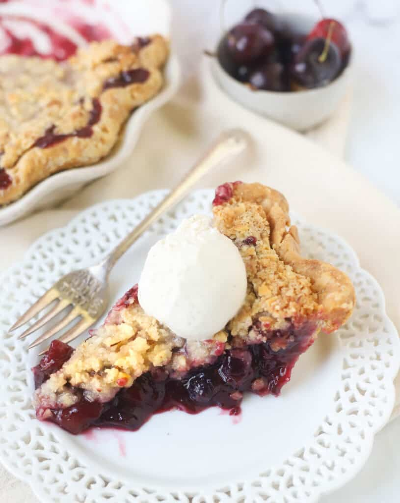 slice of cherry pie on a plate topped with vanilla ice cream