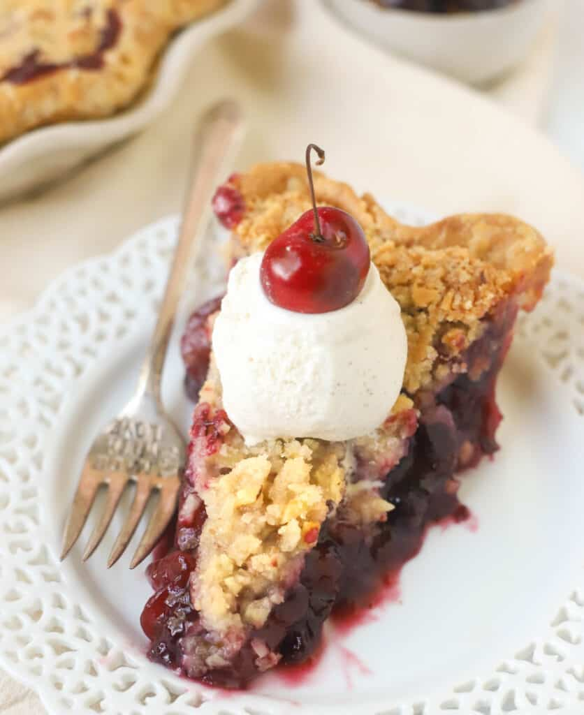 slice of cherry pie topped with a scoop of icecream and a cherry on top