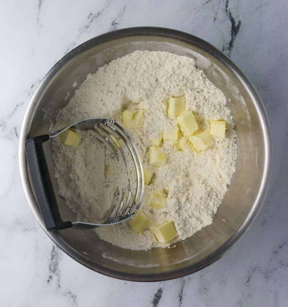 butter added to bowl of scone dry ingredients and a pastry blender in it
