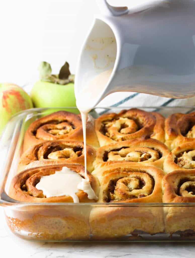 apple cinnamon rolls being drizzled with glaze