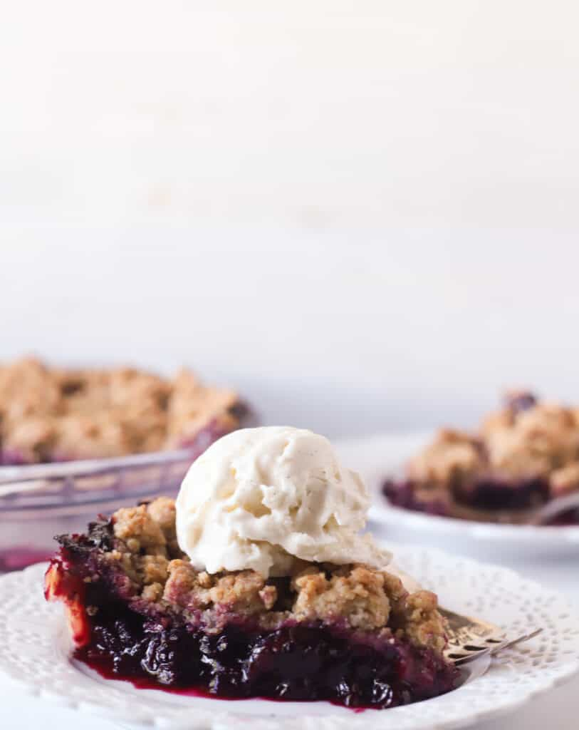 slice of blueberry pie on a plate topped with a scoop of vanilla ice cream
